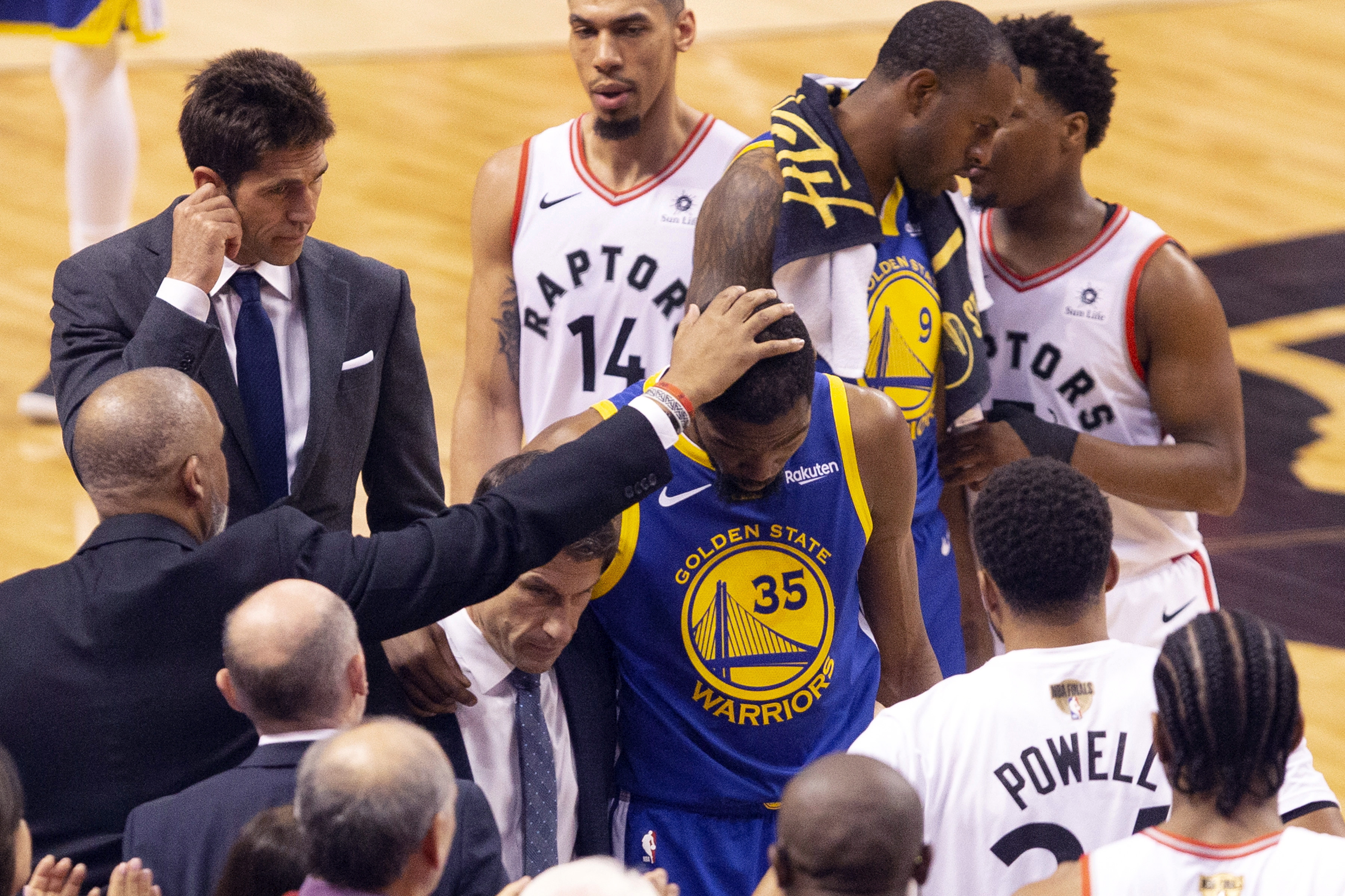 Golden State Warriors forward Kevin Durant (35) is consoled as he walks off the court after sustaining an injury during first half basketball action in Game 5 of the NBA Finals in Toronto on Monday, June 10, 2019. (Chris Young/The Canadian Press via AP)