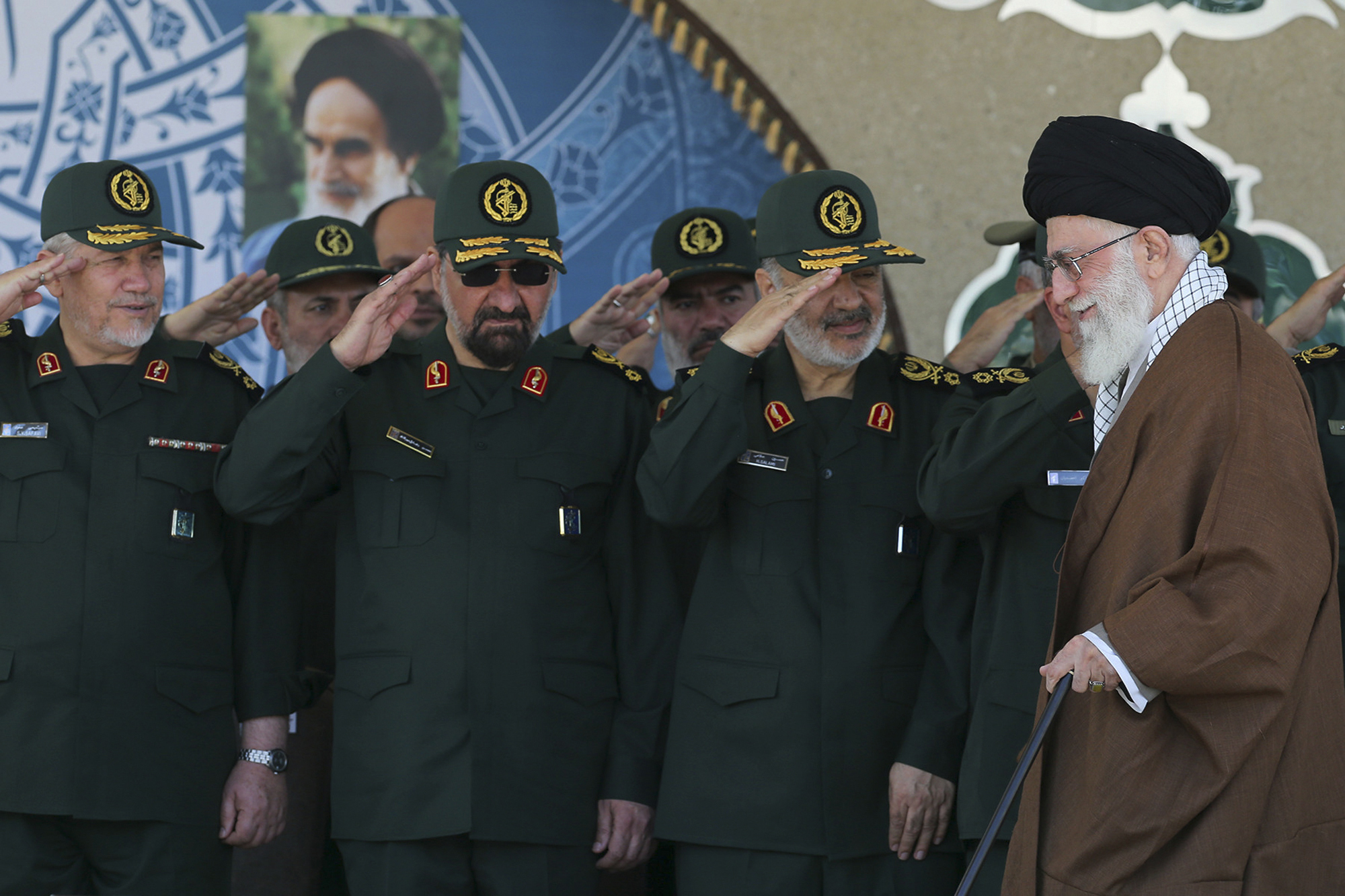 FILE- In this picture released by an official website of the office of the Iranian supreme leader, former commander of the Revolutionary Guard Mohsen Rezaei, second left, salutes Supreme Leader Ayatollah Ali Khamenei, right, while he arrives at a graduation ceremony of the Revolutionary Guard's officers, in Tehran, Iran.  Former leader of Iran's powerful Revolutionary Guard Mohsen Rezaei said on Friday, July 5, 2019, that the Islamic Republic should consider seizing a British oil tanker in response to authorities detaining an Iranian oil tanker off the coast Gibraltar. (Office of the Iranian Supreme Leader via AP, FILE)