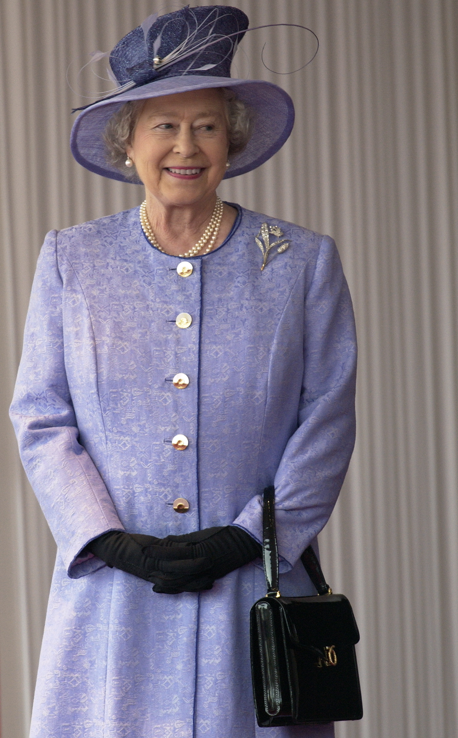 LONDON, UNITED KINGDOM - NOVEMBER 19:  Queen Elizabeth Ll Smiling During The State Visit Of The American President At Buckingham Palace.  The Queen Is Wearing A Mauve Coat With Matching Hat Which She Has Accessorized With Black Gloves And A Black Launer Handbag.  (Photo by Tim Graham Photo Library via Getty Images)
