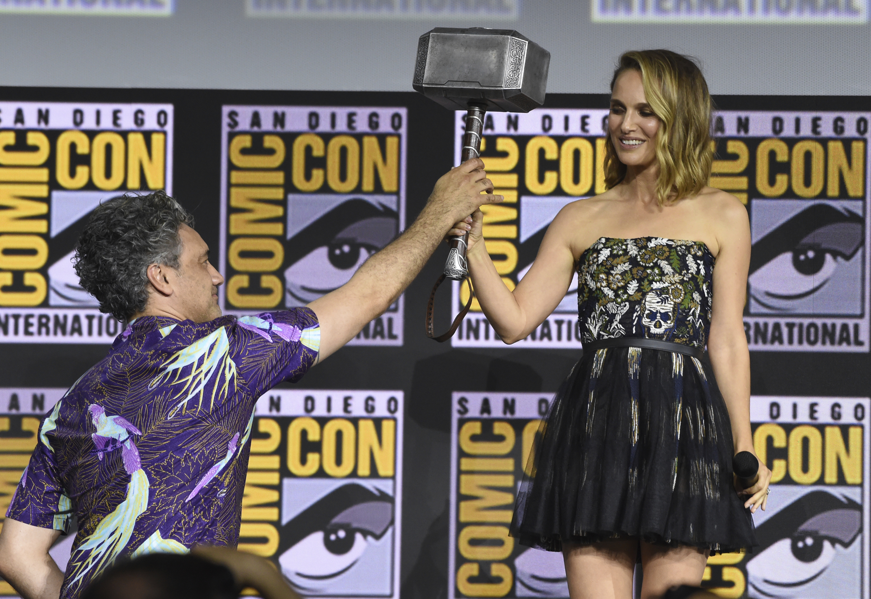 """Director Taika Waititi hands the Thor hammer to Natalie Portman during the """"Thor Love And Thunder"""" portion of the Marvel Studios panel on day three of Comic-Con International on Saturday, July 20, 2019, in San Diego. (Photo by Chris Pizzello/Invision/AP)"""