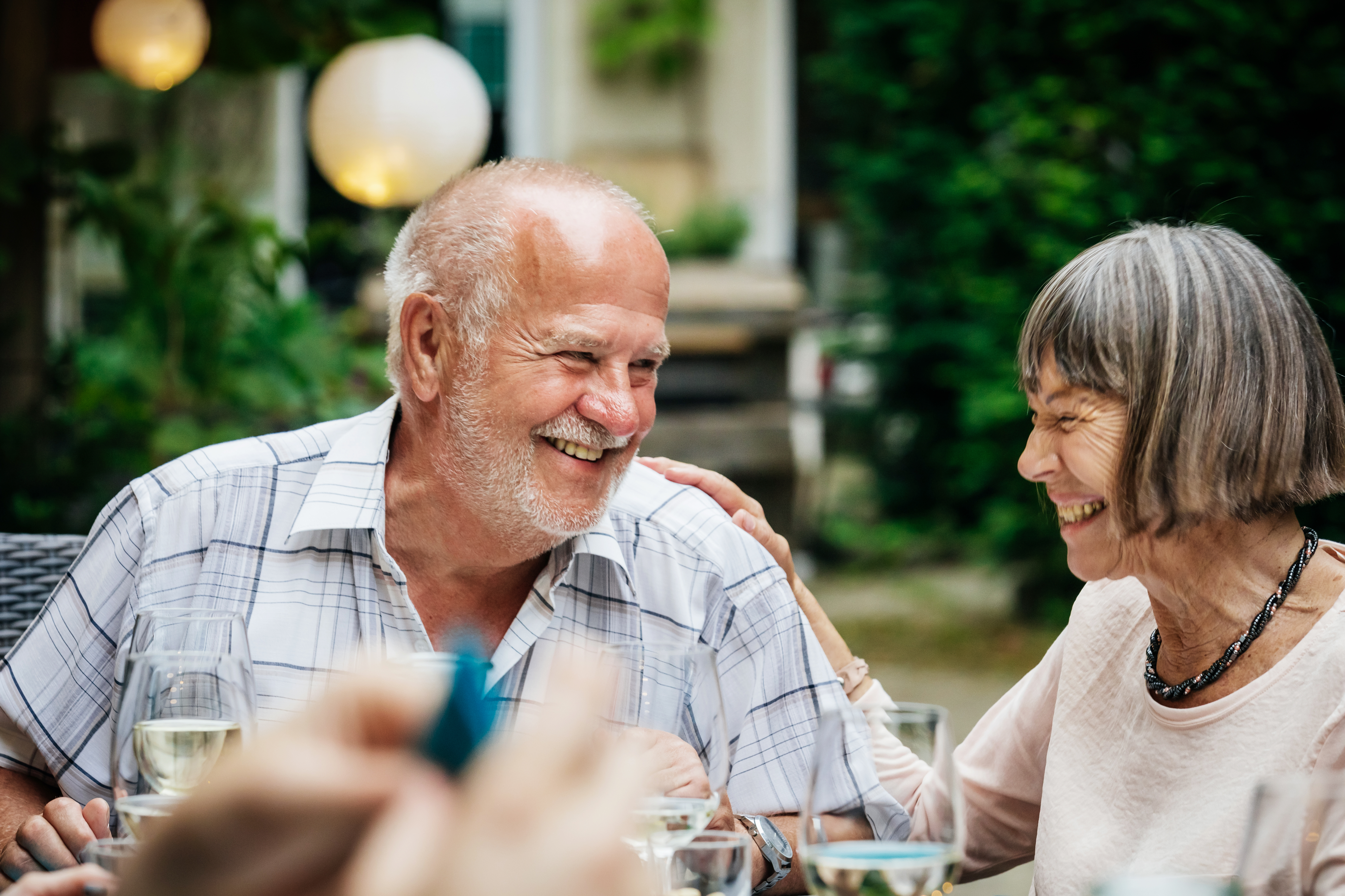 An elderly couople smiling and drinking at a family barbecue in a courtyard.