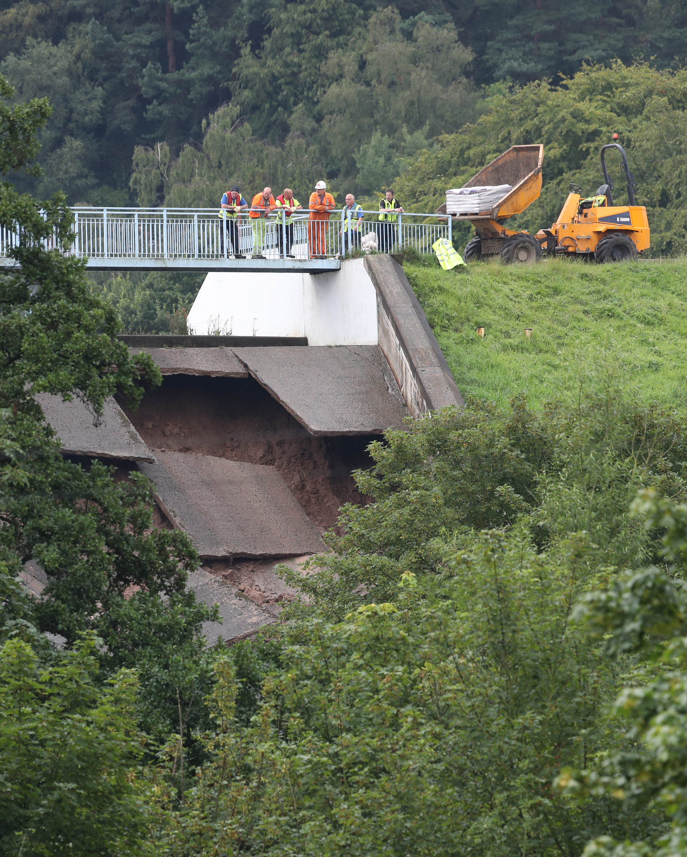 A team of men look at the damage to the wall of Toddbrook Reservoir near the village of Whaley Bridge, Cheshire, after it was damaged in heavy rainfall.