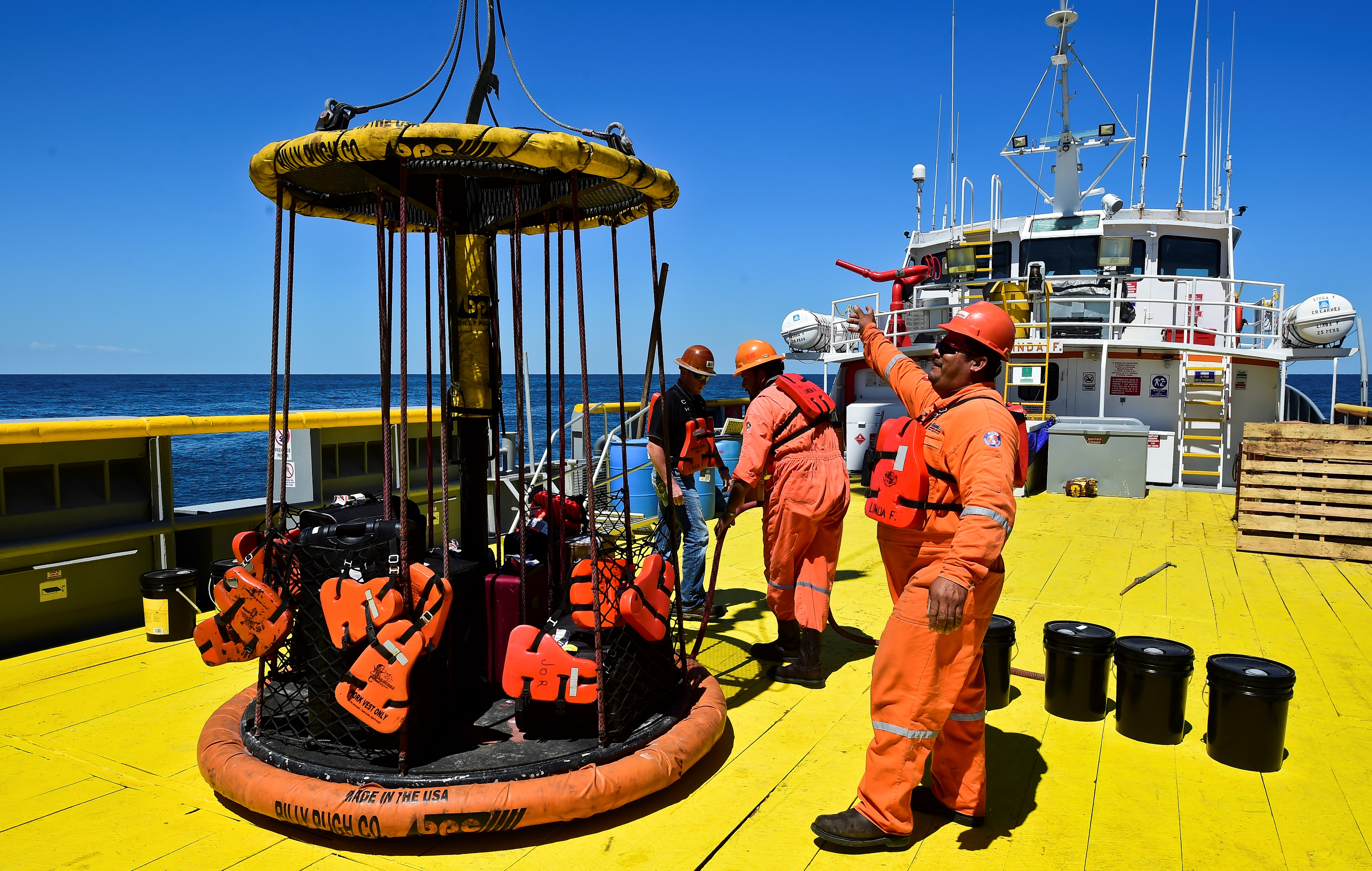 Sailors and workers load members luggage onto the L/B MYRTLE Offshore Support Vessel -a scientific plataform working in the Gulf of Mexico- in front of the Yucatan State, in Mexico, on May 7, 2016.  A scientific mission led by IODP (International Ocean Discovery Program) studies the Chicxulub impact crater on the Gulf of Mexico, created after an asteroid crashed 66 million years ago. The research aims to find evidence of the origin of the universe and the evolution of life on Earth. / AFP / RONALDO SCHEMIDT        (Photo credit should read RONALDO SCHEMIDT/AFP/Getty Images)