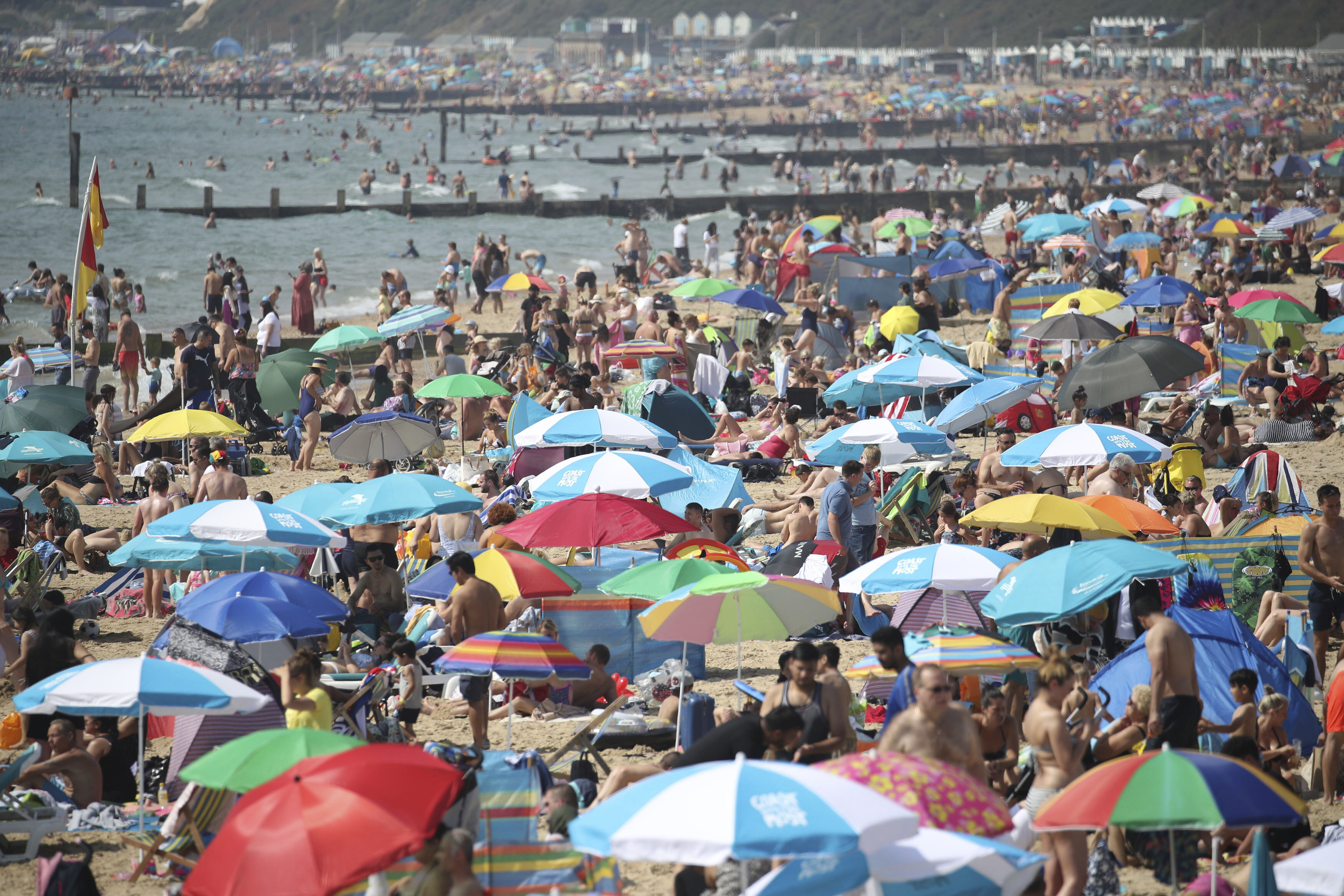 People enjoying the warm weather on Bournemouth beach, as a bank holiday heatwave will see most of Britain sizzling in sunshine with possible record temperatures, the Met Office has said. Saturday Aug, 24, 2019. |(|Andrew Matthews/PA via AP)