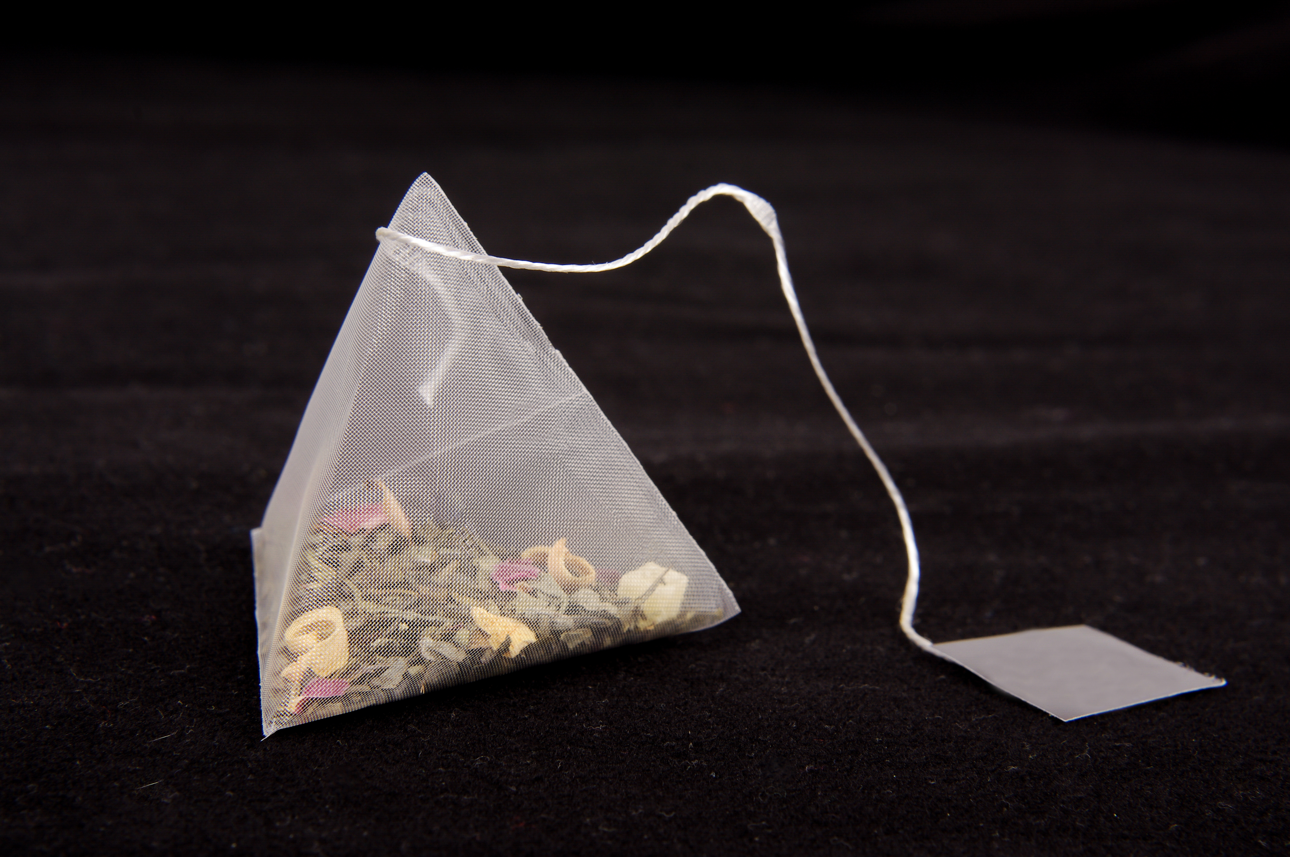 Teabag in the pyramid shape on the dark background