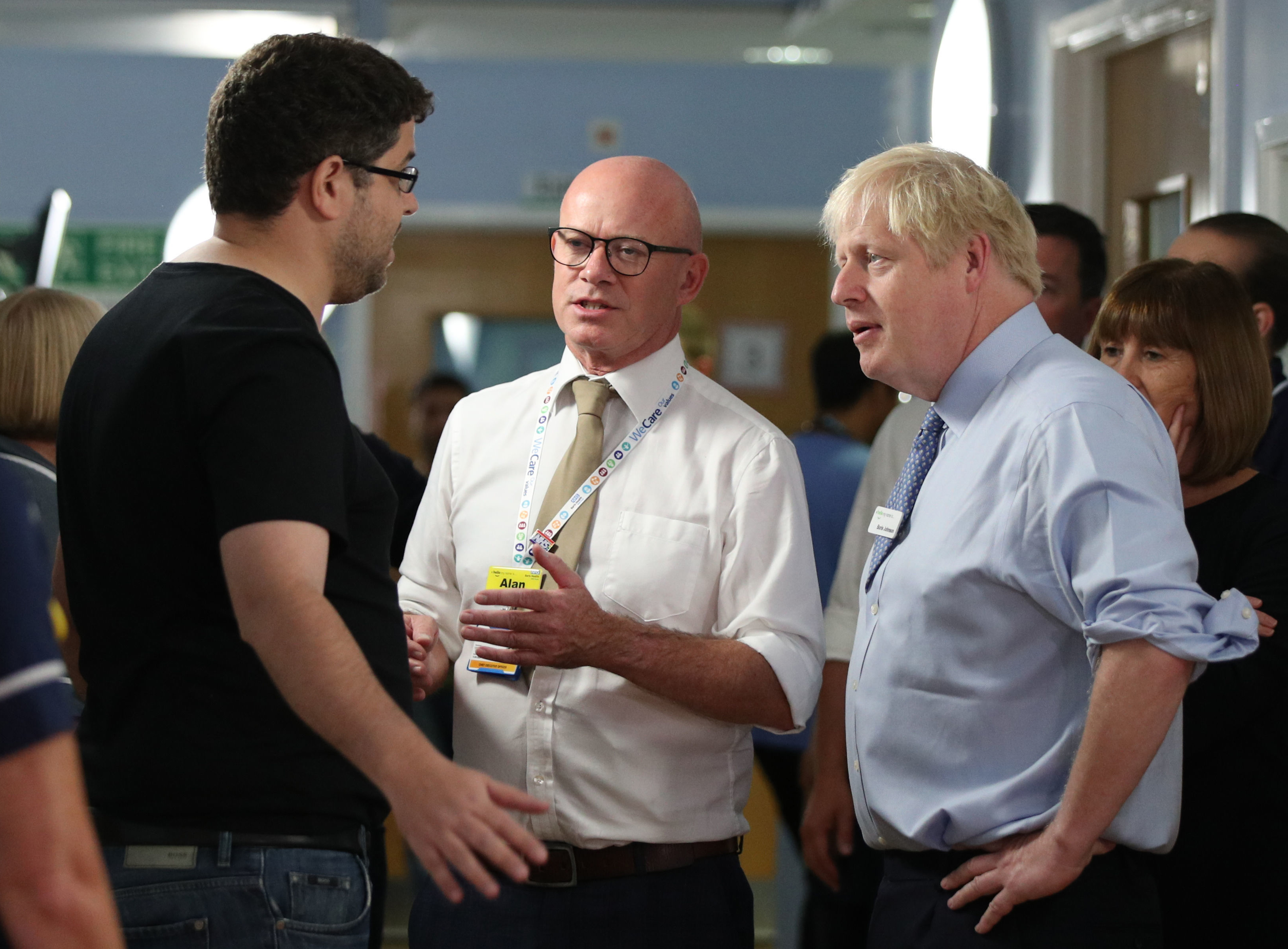 Britain's Prime Minister Boris Johnson (R) listens as the father of a young girl.