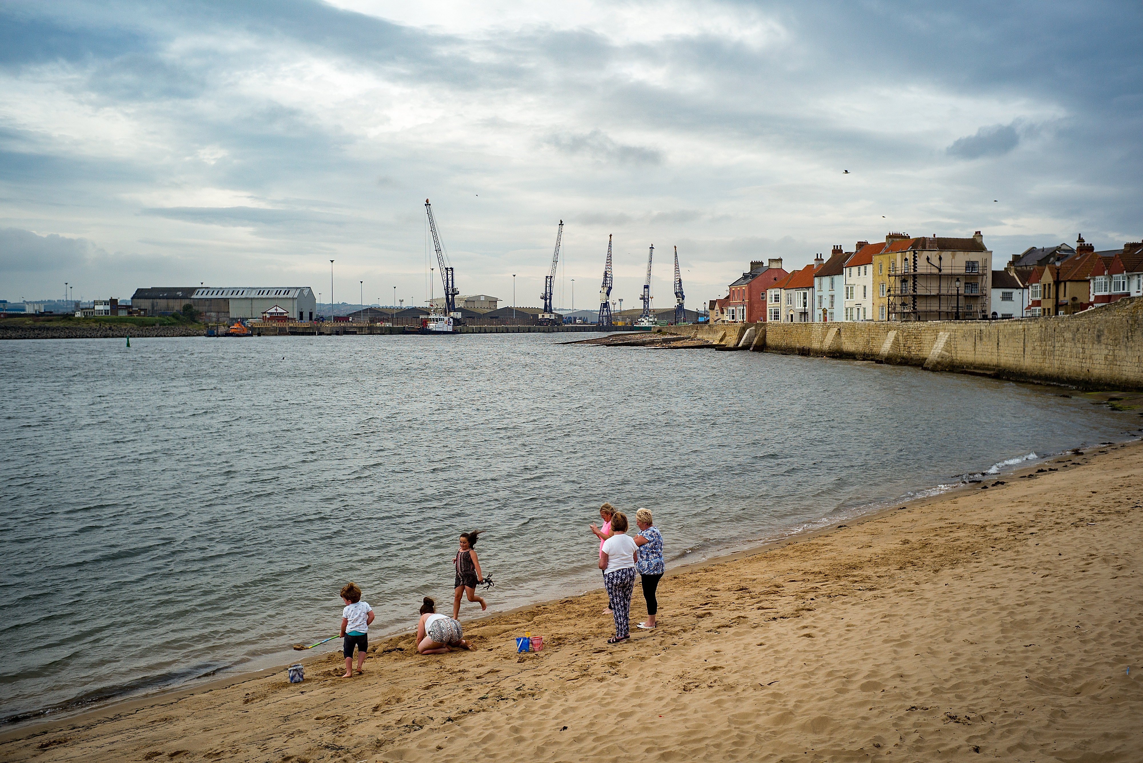 HARTLEPOOL, ENGLAND - SEPTEMBER 04:  Locals spend time on the beach near the docks in the Headland area of Hartlepool,on September 4, 2017 in Hartlepool, England. Hartlepool in the North East of England is one of the many coastal towns lagging behind inland areas with some of the worst levels of economic and social deprivation in the country. The Social Market Foundation (SMF) found that 85% of Great Britain's 98 coastal local authorities had pay levels below the national average for 2016. The government has announced that it will give 40 million GBP to encourage tourism and boost employment in the areas.  (Photo by Christopher Furlong/Getty Images)