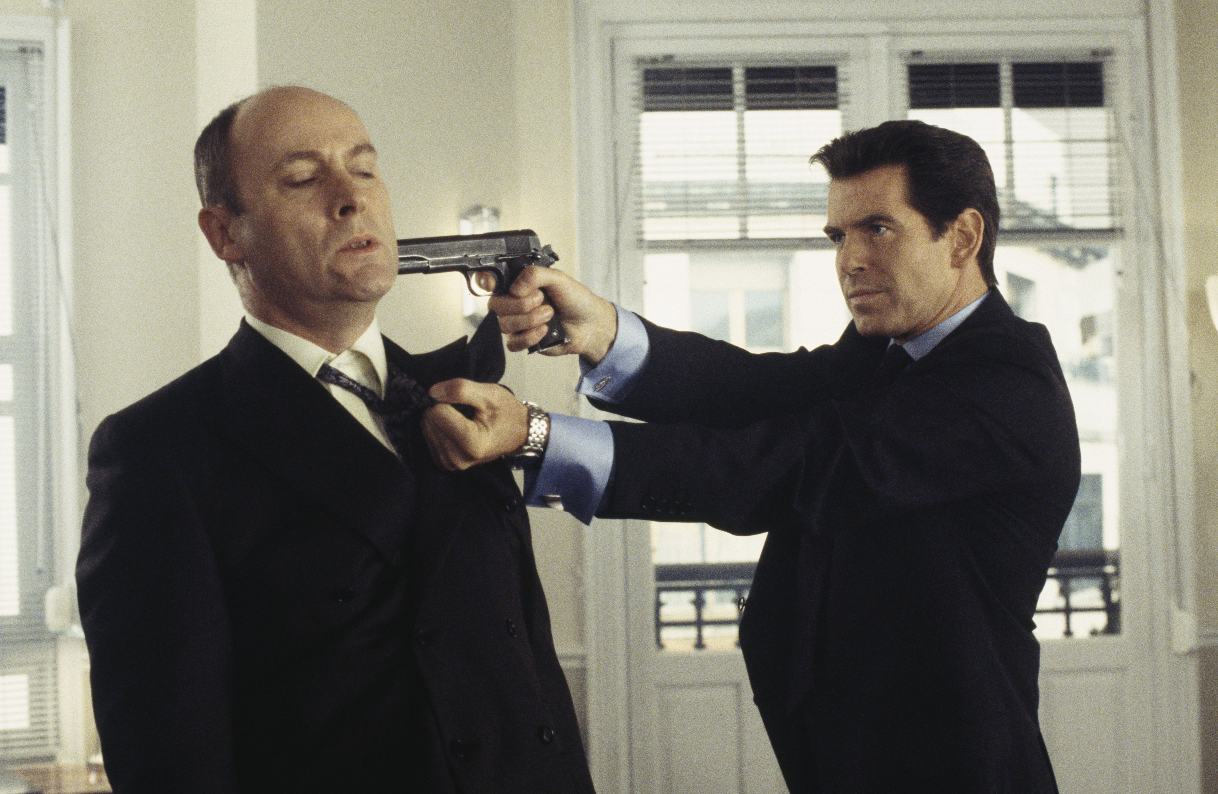 Irish actor Pierce Brosnan as 007 in the James Bond film 'The World Is Not Enough', 1999. Here he threatens Swiss banker Lachaise, played by English actor Patrick Malahide, with a Colt M1911A1 semi-automatic pistol. (Photo by Keith Hamshere/Getty Images)