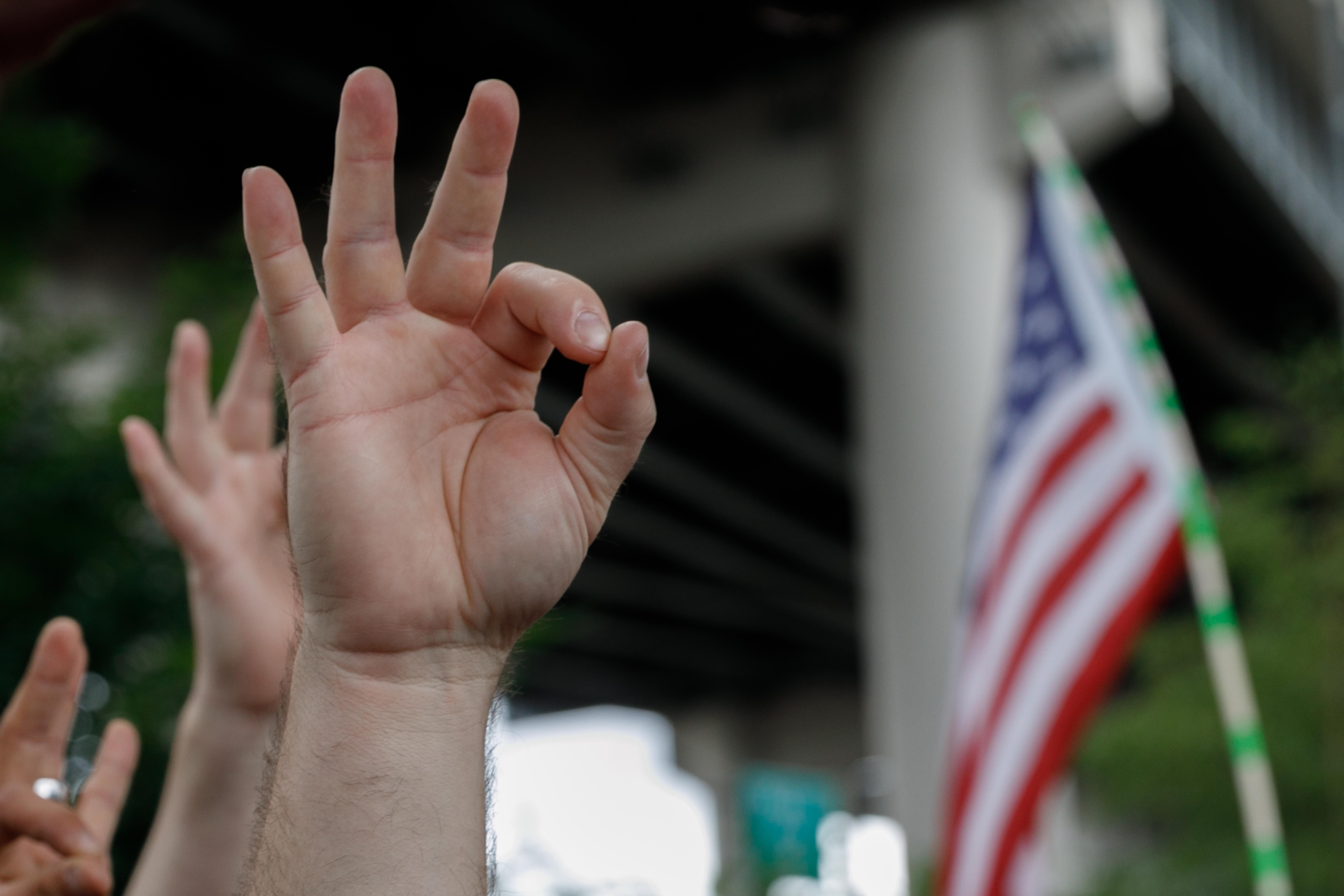"""A far-right demonstrator makes the OK hand gesture believed to have white supremacist connotations during """"The End Domestic Terrorism"""" rally at Tom McCall Waterfront Park on August 17, 2019 in Portland, Oregon. - No major incidents were reported on Saturday afternoon in Portland (western USA) during a far-right rally and far-left counter-demonstration, raising fears of violent clashes between local authorities and US President Donald Trump, who was monitoring the event """"very closely"""". (Photo by John Rudoff / AFP)        (Photo credit should read JOHN RUDOFF/AFP/Getty Images)"""