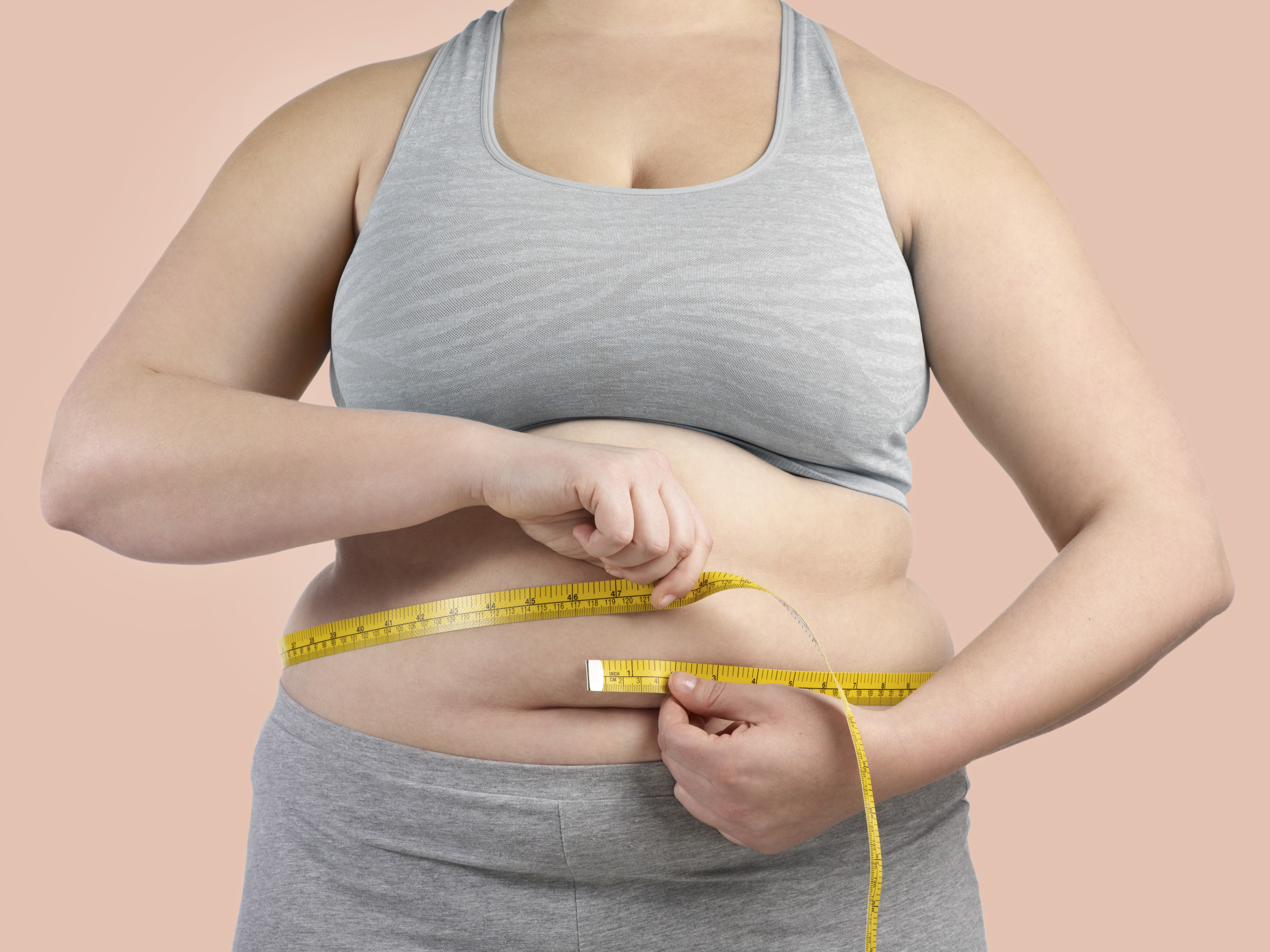 Overweight woman measuring her waist with a tape measure.