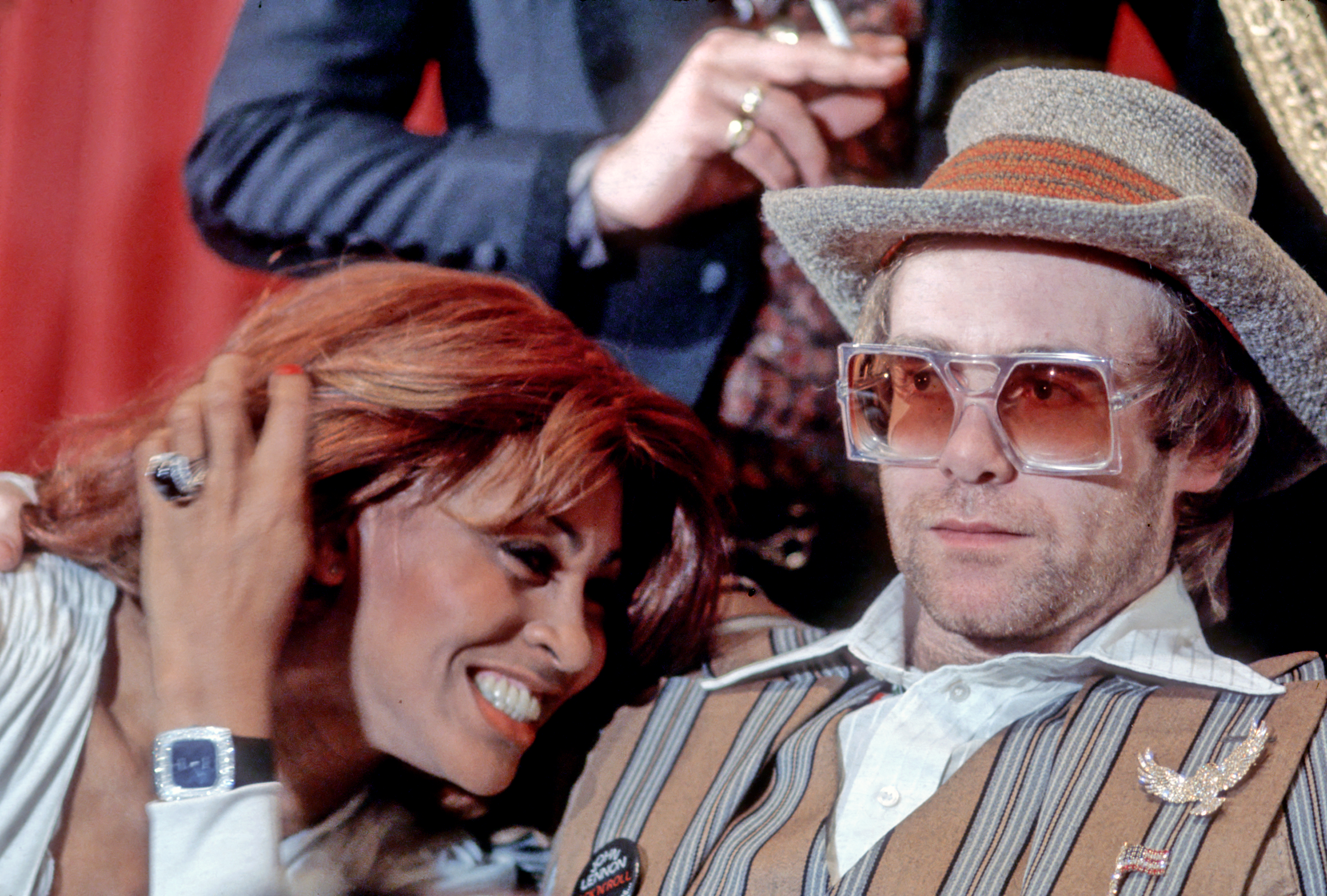 """MARCH 18: Rock and roll singer Tina Turner snuggles up to fellow performer Elton John during a press conference  for the release of the rock group """"The Who's"""" rock opera film """"Tommy"""" in which they appear on March 18, 1975. (Photo by Michael Ochs Archives/Getty Images)"""