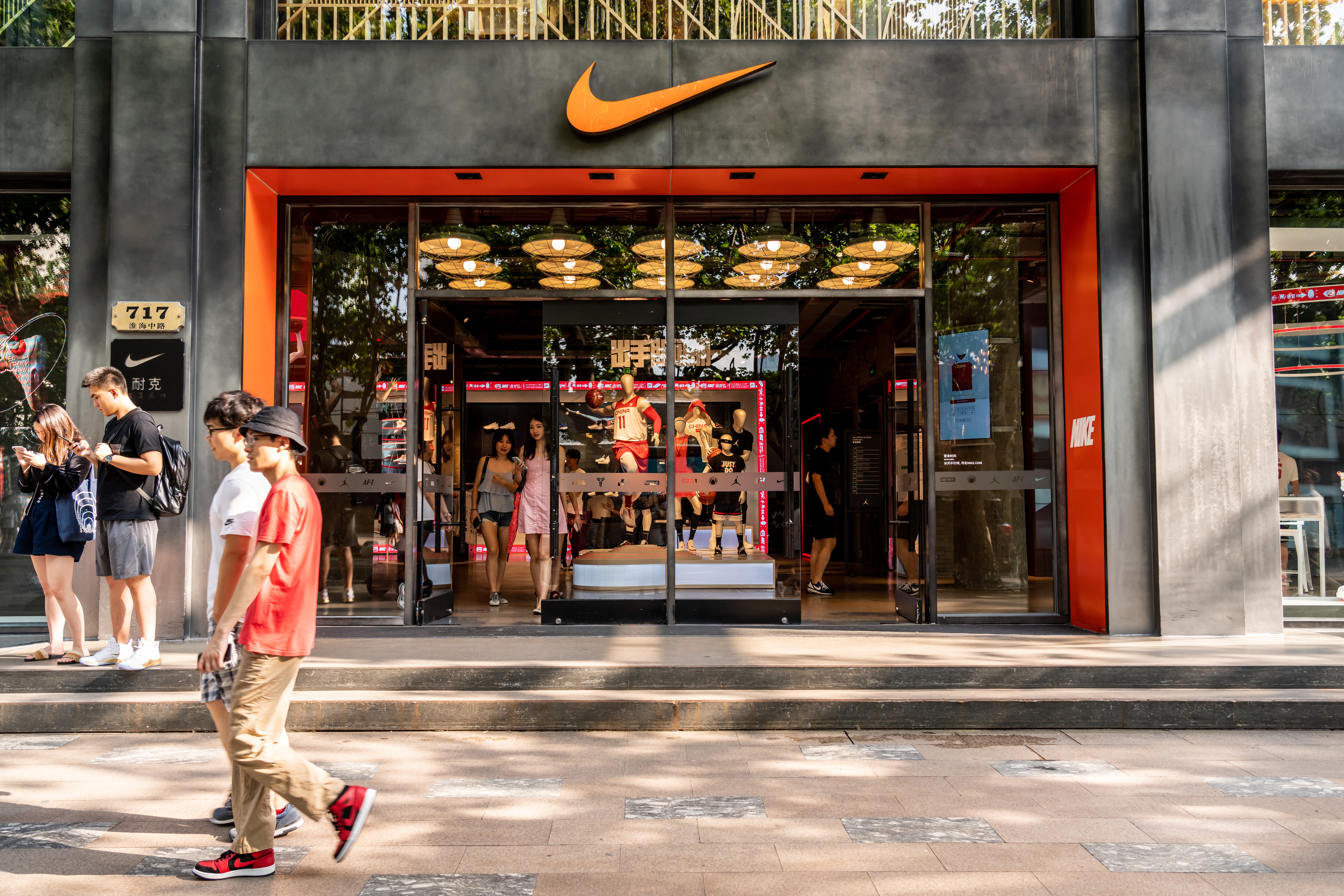 SHANGHAI, CHINA - 2019/09/07: Pedestrians walk past an American multinational sportswear corporation Nike store in Shanghai. (Photo by Alex Tai/SOPA Images/LightRocket via Getty Images)