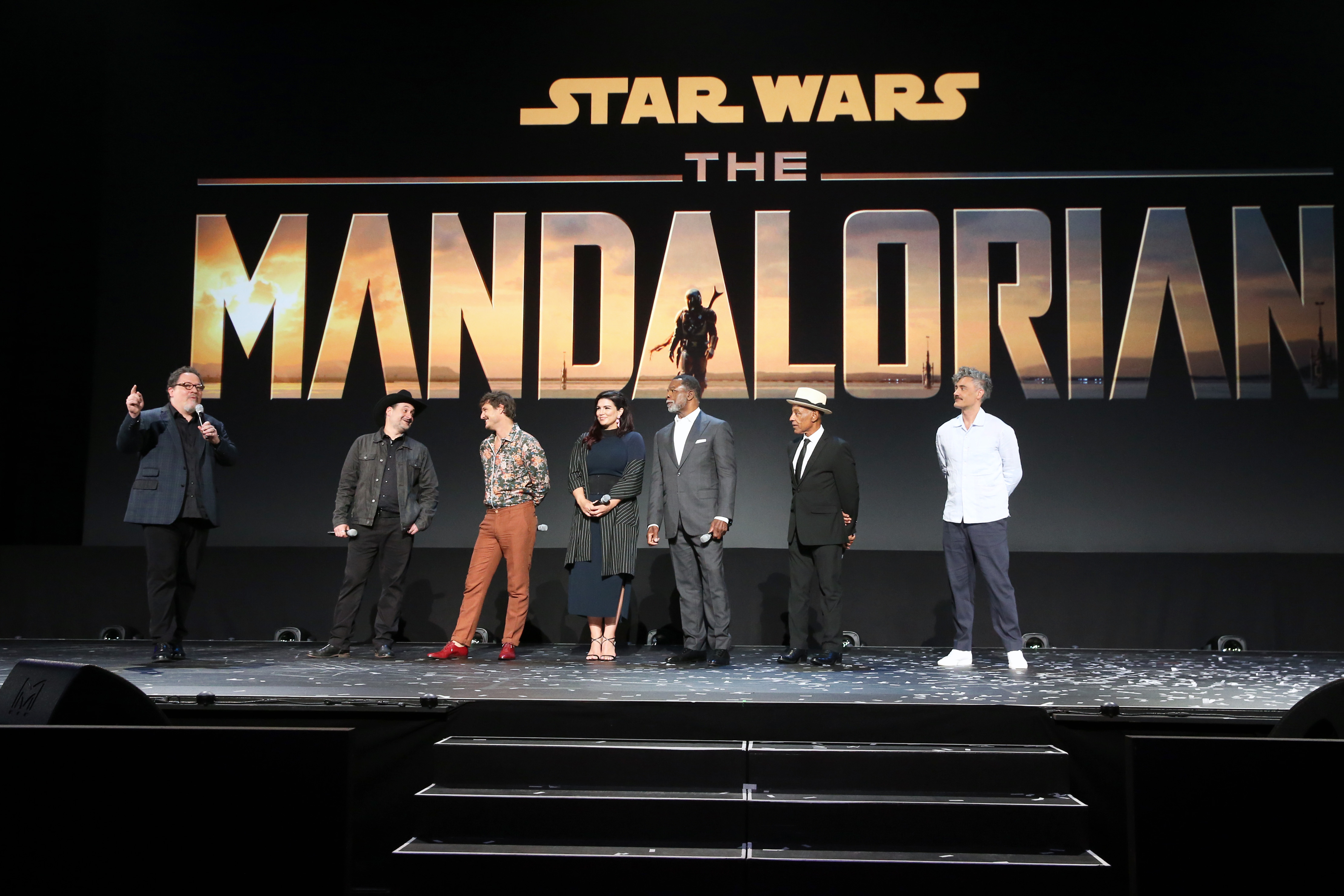 ANAHEIM, CALIFORNIA - AUGUST 23: (L-R) Executive producer/writers Jon Favreau, Dave Filoni, Pedro Pascal, Gina Carano, Carl Weathers, Giancarlo Esposito and Taika Waititi of 'The Mandalorian' took part today in the Disney+ Showcase at Disney's D23 EXPO 2019 in Anaheim, Calif.  'The Mandalorian' will stream exclusively on Disney+, which launches November 12. (Photo by Jesse Grant/Getty Images for Disney)
