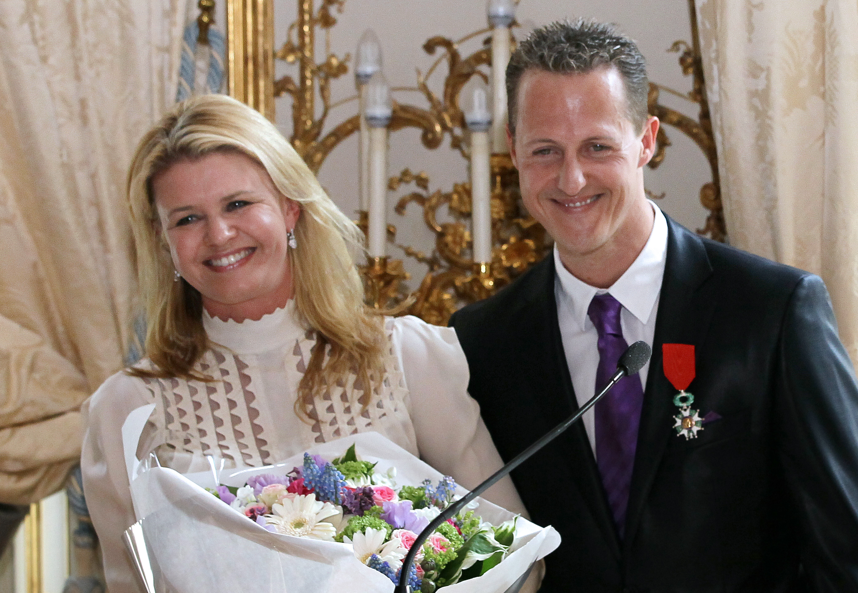 German Formula 1 pilot, Michael Schumacher poses with his wife Corinna after he was awarded with the French Legion of Honor by French Prime Minister Francois Fillon on April 29, 2010 at the Hotel Matignon in Paris. AFP PHOTO THOMAS COEX        (Photo credit should read THOMAS COEX/AFP/GettyImages)