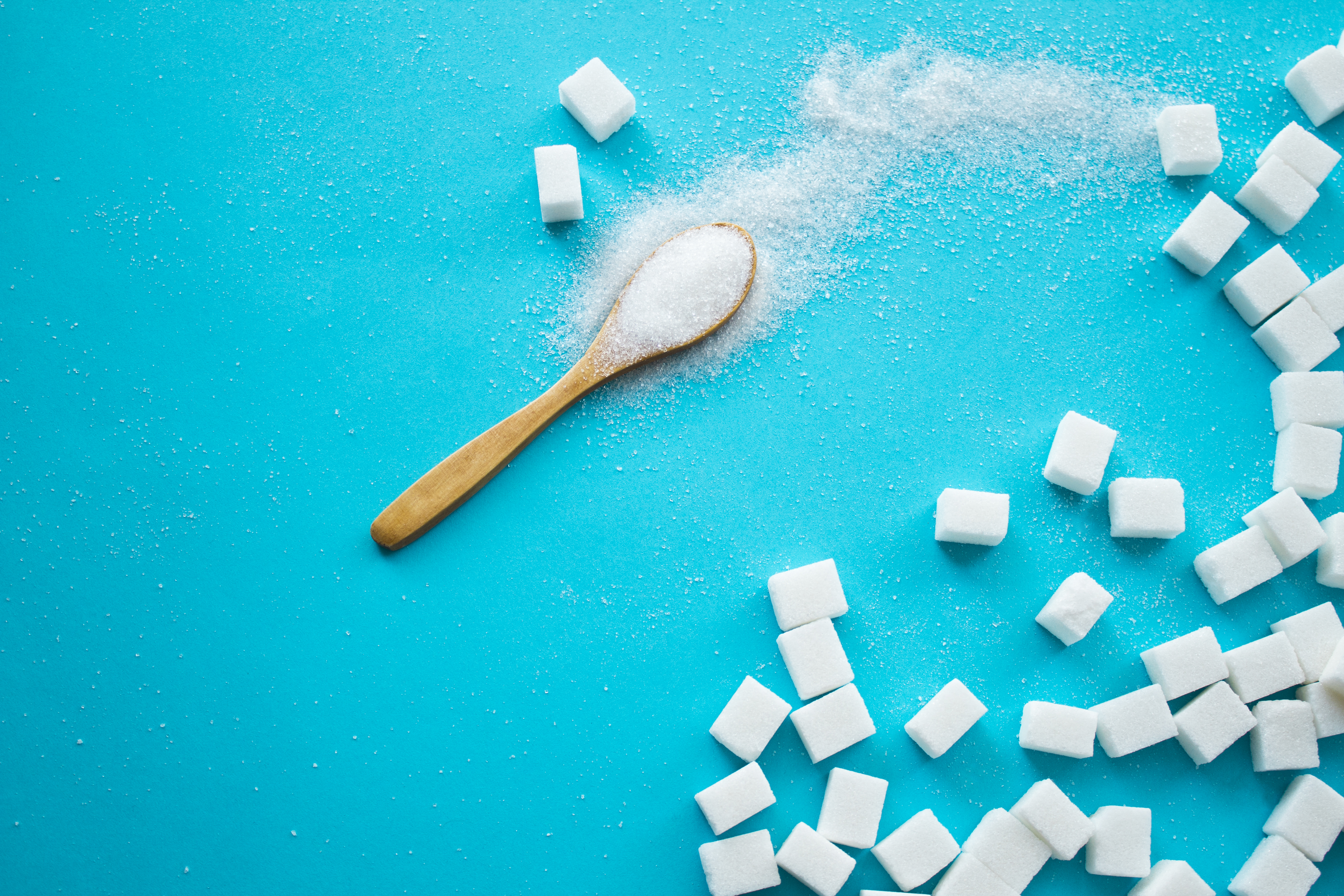 White sugar with spoon on blue background. Top view.