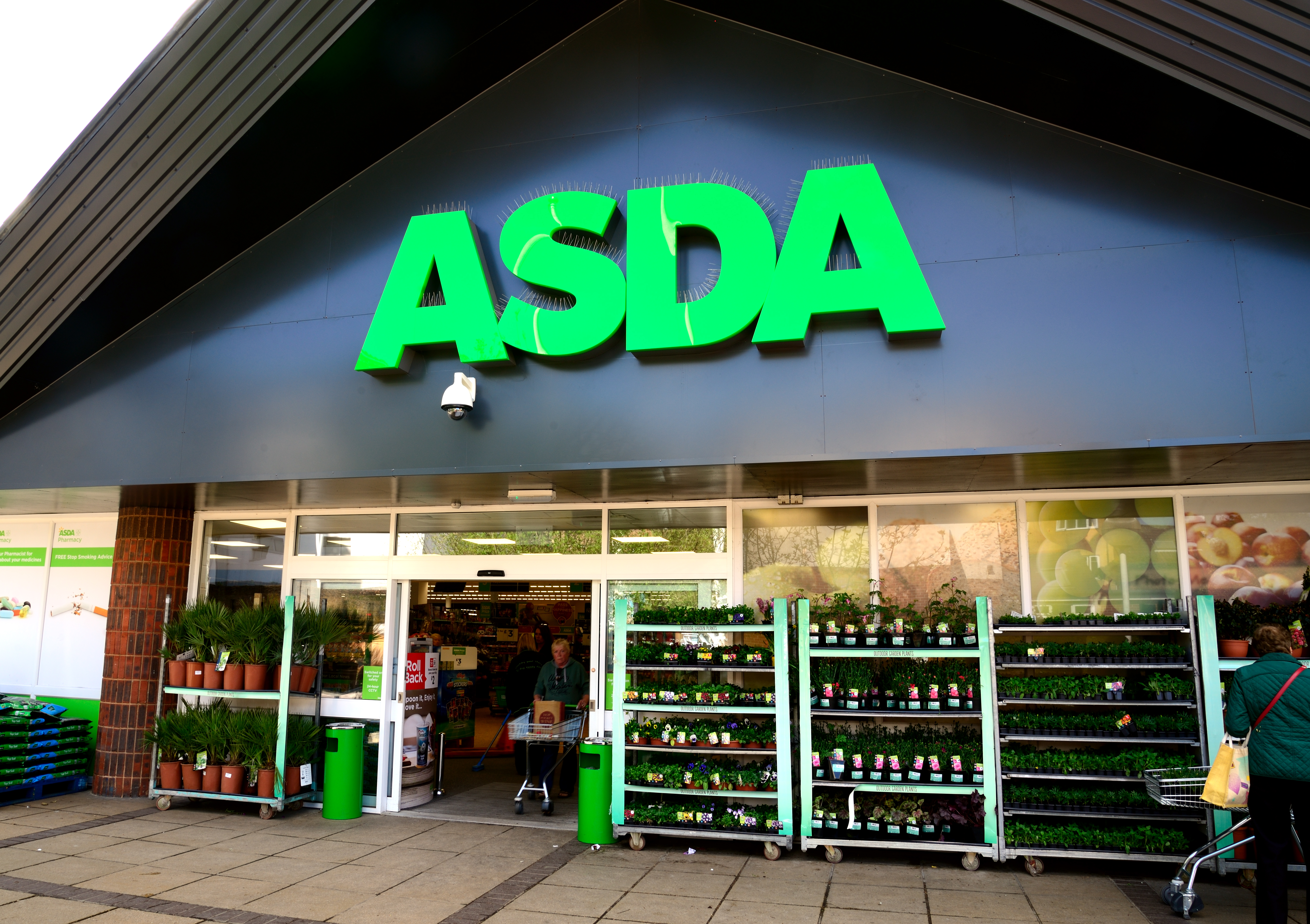Waterlooville, UK - May 2, 2018: Asda Stores Ltd. trading as Asda, is a British supermarket retailer. The logo is prominent above the glass fronted store-front.  Advertising, products and Sshoppers are all visible.