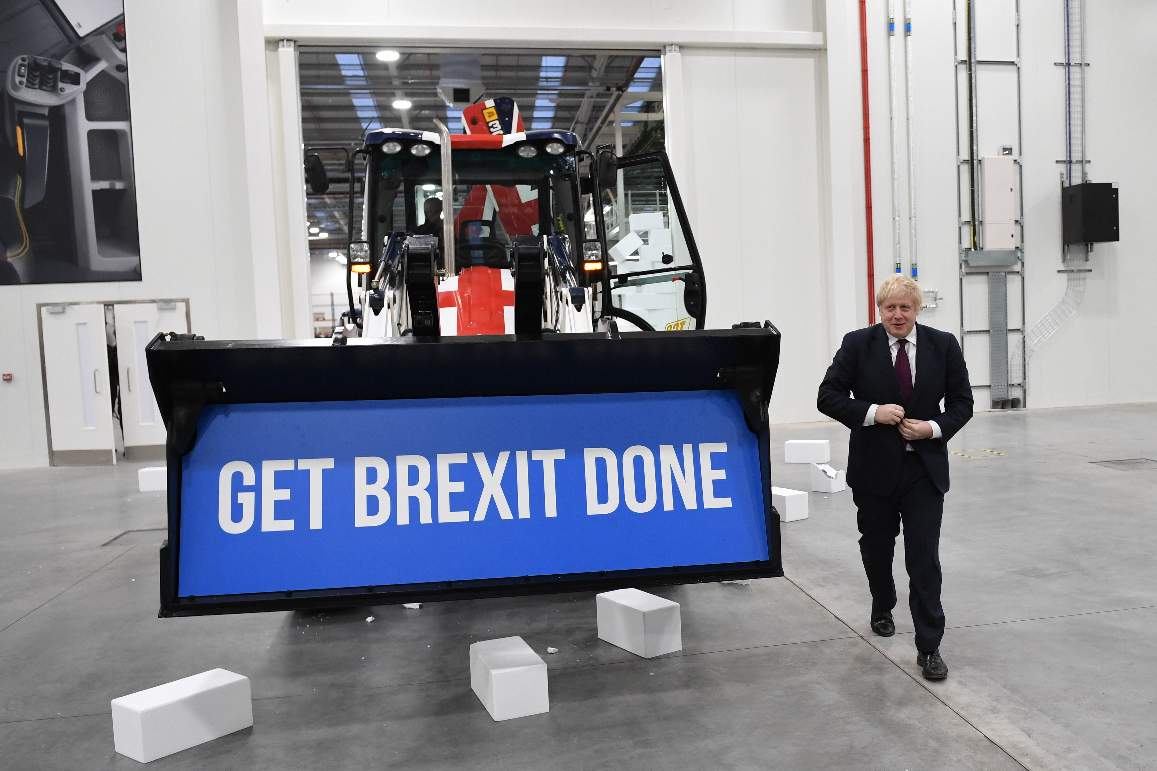 """Prime Minister Boris Johnson walks away after driving a Union flag-themed JCB, with the words """"Get Brexit Done"""" inside the digger bucket, through a fake wall emblazoned with the word """"Gridlock"""", during a visit to JCB cab manufacturing centre in Uttoxeter, while on the General Election campaign trail."""
