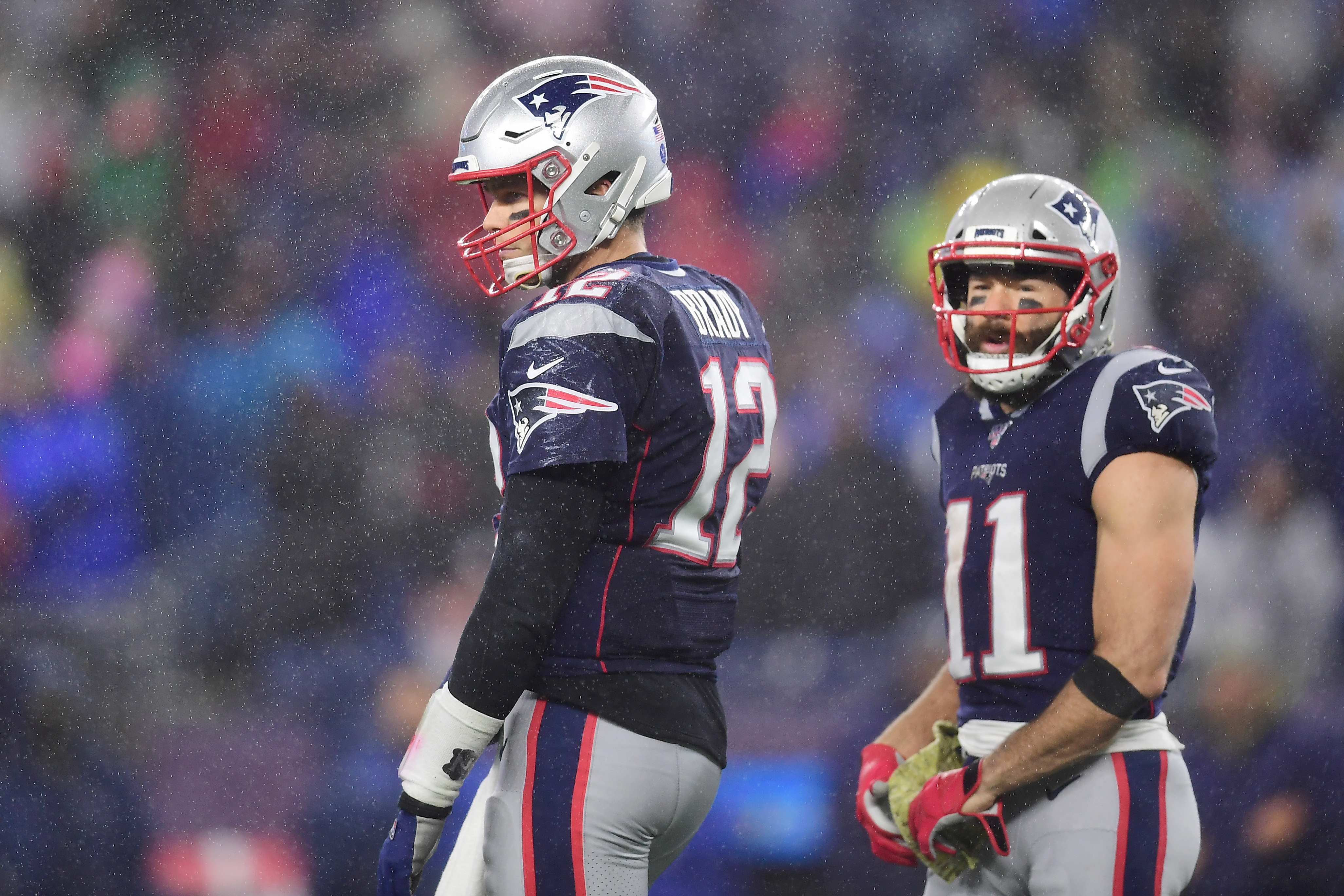 Tom Brady and Julian Edelman on the field together in Patriots uniforms.