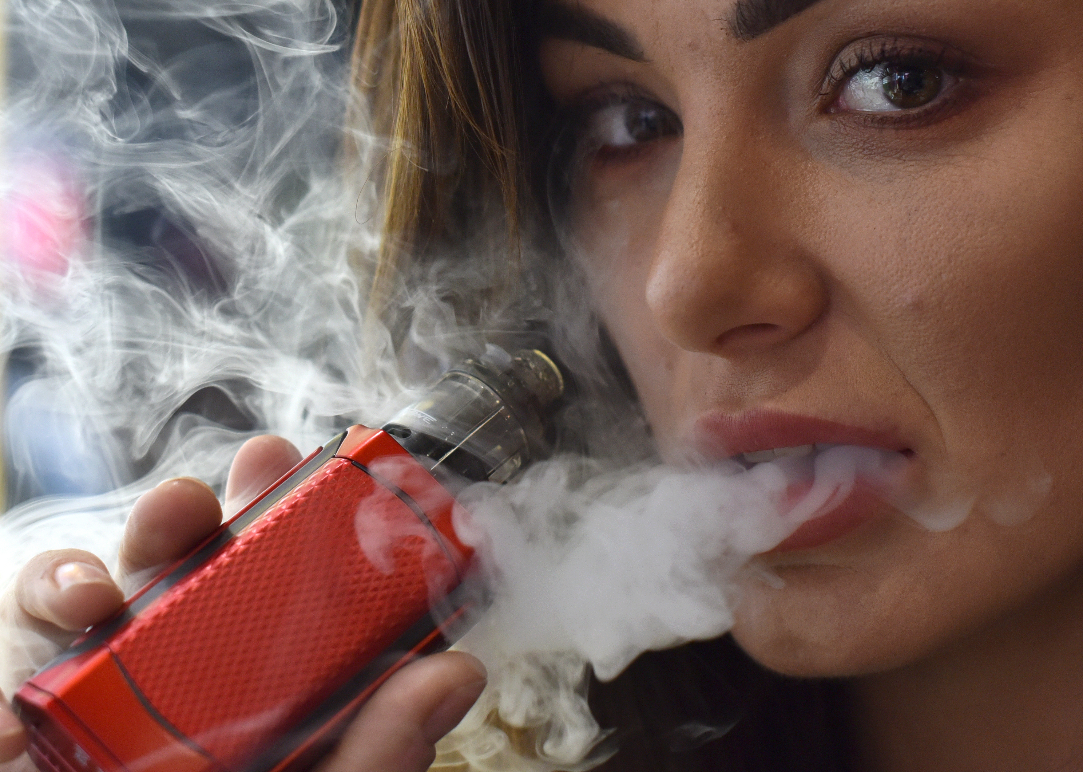 LONDON, ENGLAND - APRIL 12: Promotional person vapes on the Reds, Ejuice stand during Vape Jam 2019 at ExCel on April 12, 2019 in London, England. Vape Jam UK, the premier Electronic Cigarette and E-Liquid trade show brings key industry players, leading manufacturers, consumers, hobbyists and people looking for an alternative to tobacco. (Photo by John Keeble/Getty Images)
