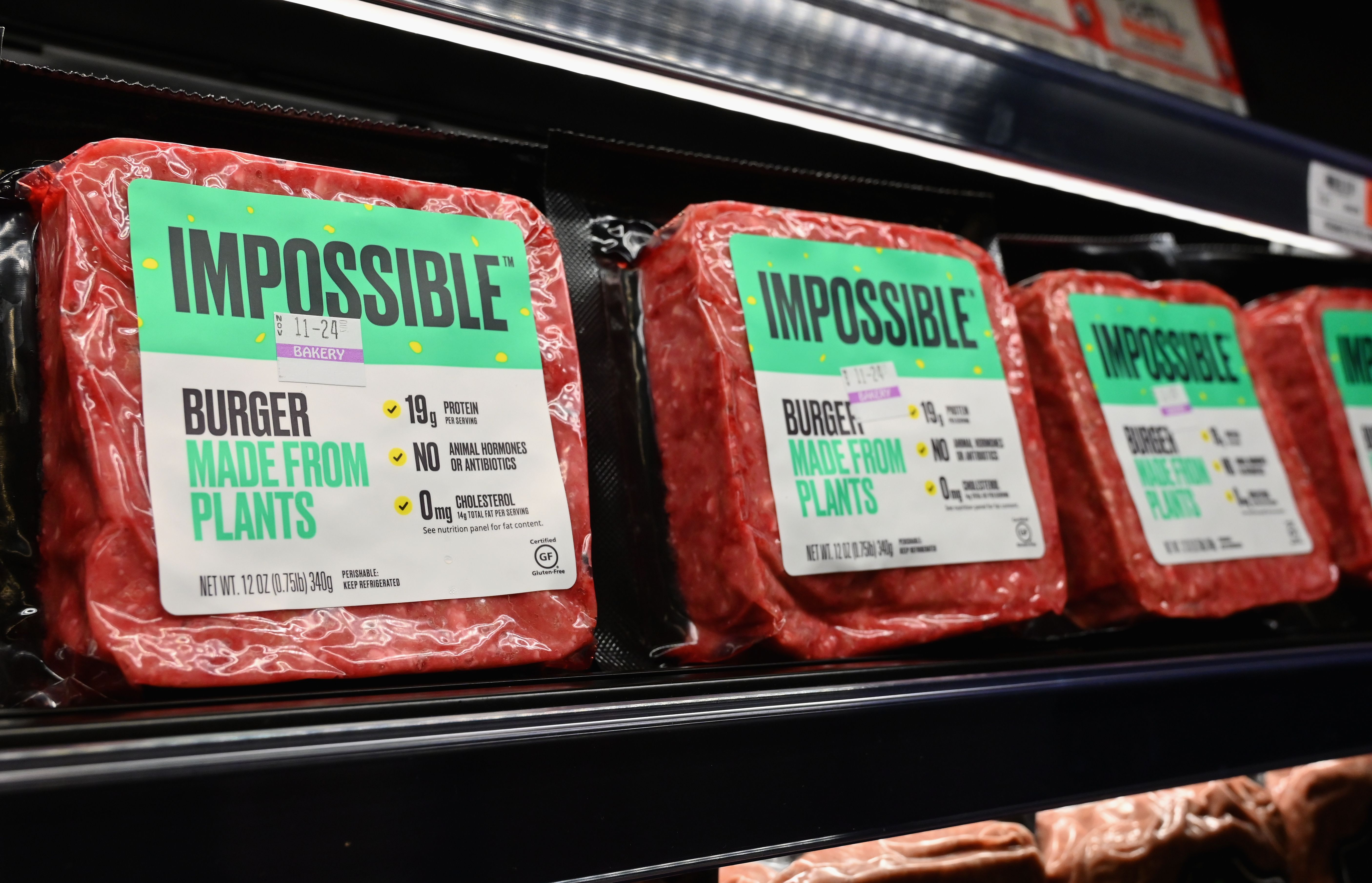 """Impossible Foods"" burgers made from plant-based substitutes for meat products sit on a shelf for sale on November 15, 2019 in New York City. - Vegetarian alternatives to burgers and sausages, revived by start-ups like Beyond Meat and Impossible Burger, are enjoying a certain enthusiasm that meat giants also want to enjoy. Since this summer, the world leader in the JBS sector has been marketing a soy burger in Brazil that includes beetroot, garlic and onions, with a look similar to a rare minced steak. In the US, the largest meat producer Tyson Foods launched a new line of products in June based on plants or mixing meat and vegetables. Its competitors Hormel Foods, Perdue Farms or Smithfield, have similar initiatives. (Photo by Angela Weiss / AFP) (Photo by ANGELA WEISS/AFP via Getty Images)"