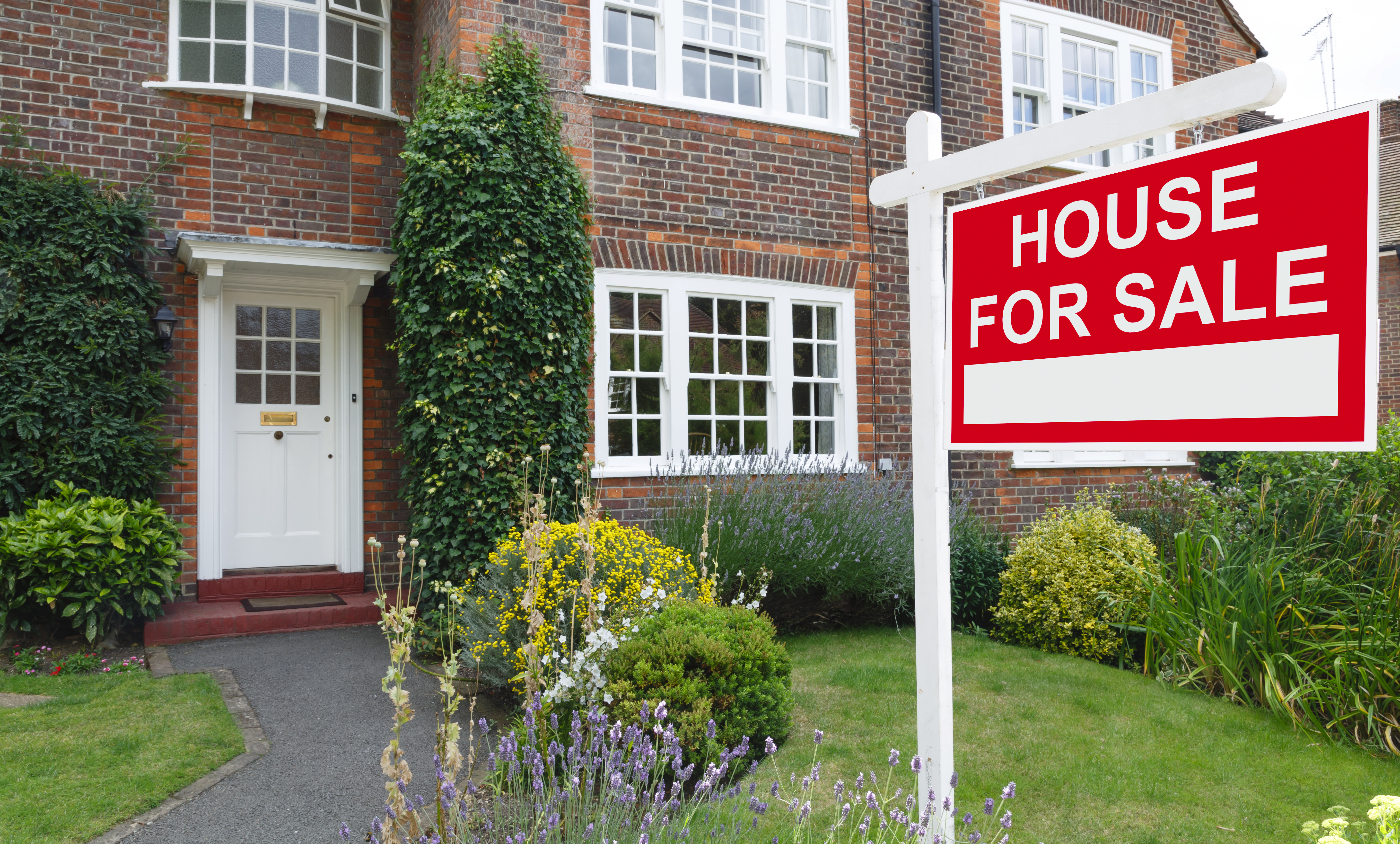 For sale sign outside a house in an affluent suburb of London
