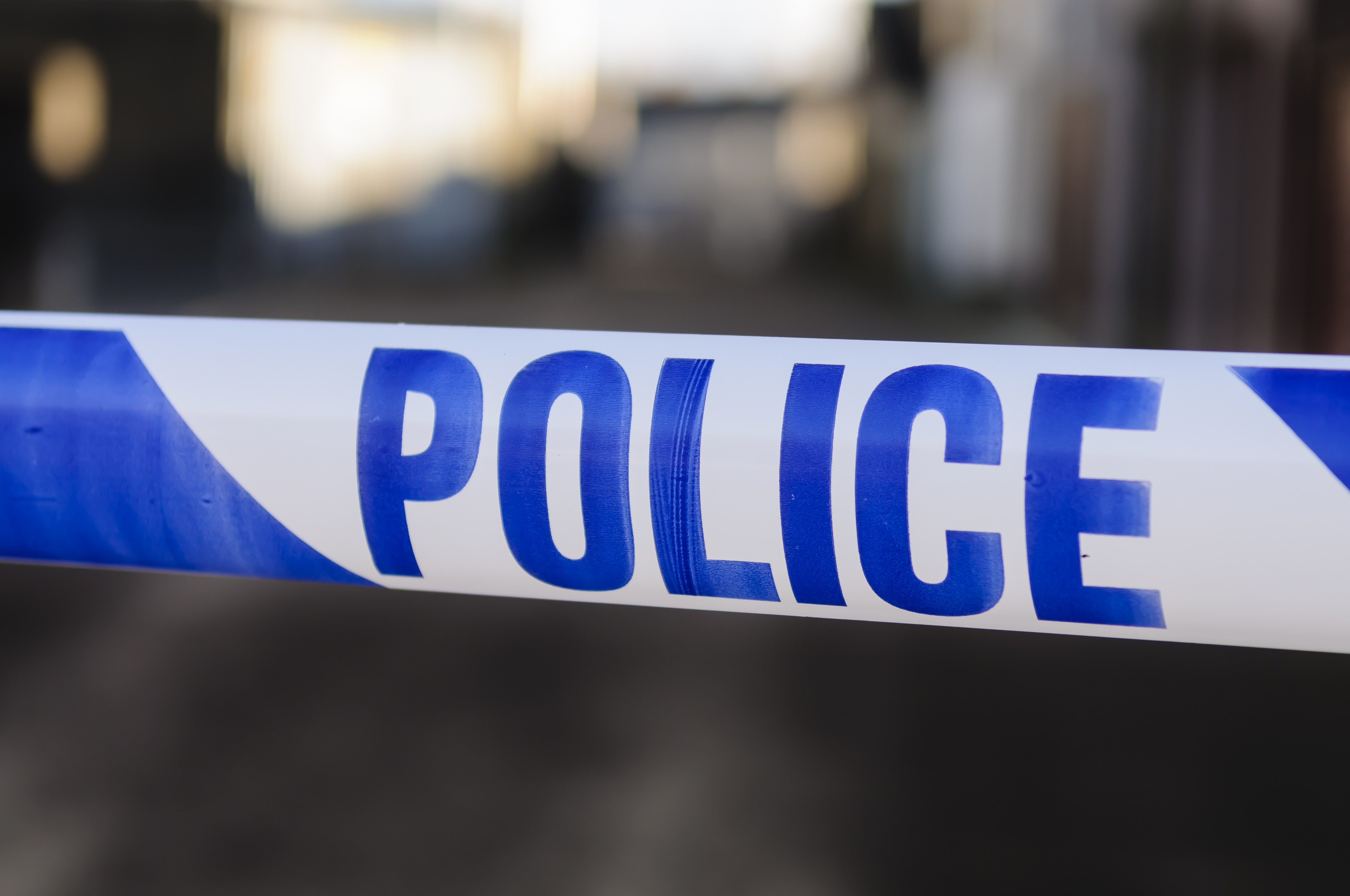 Police tape at the cordon across a crime scene