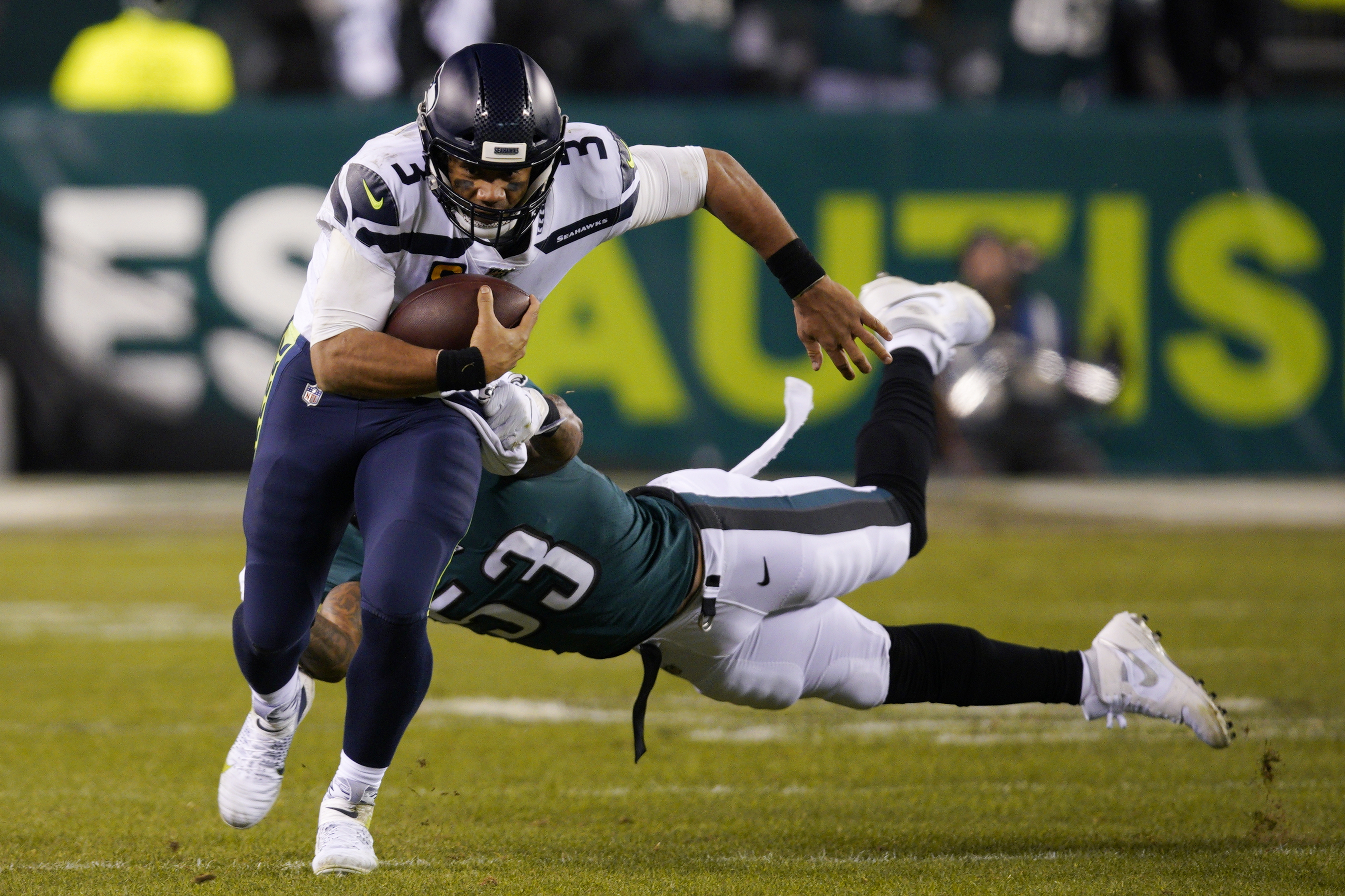 Seahawks quarterback Russell Wilson (3) rushes past Philadelphia's Nigel Bradham on Sunday. (AP Photo/Chris Szagola)