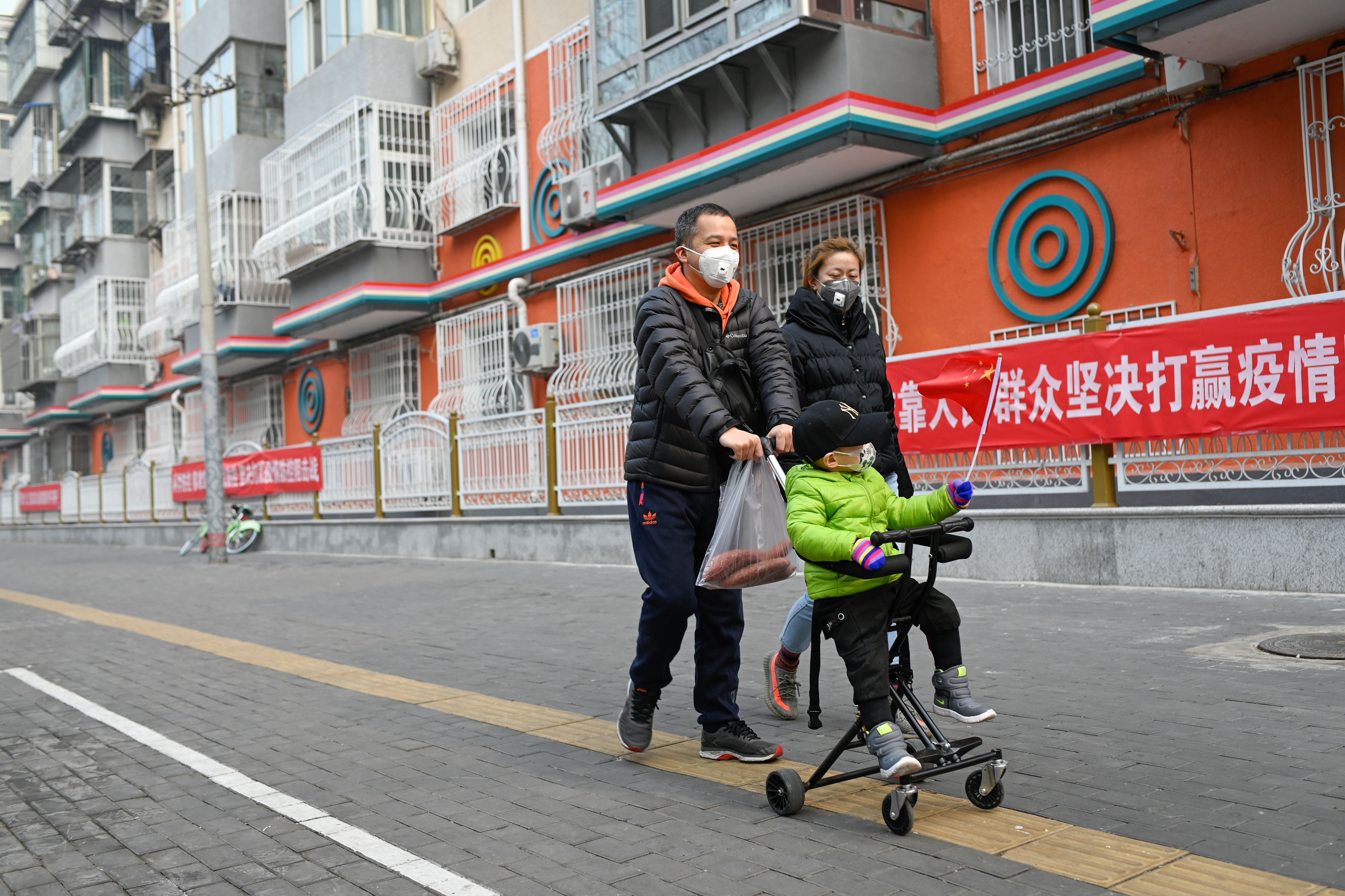A boy wearing a face mask waves a Chinese national flag as he sits on a stroller in Beijing on February 13, 2020. - The number of deaths and new cases from China's COVID-19 coronavirus outbreak spiked dramatically on February 13 after authorities changed the way they count infections in a move that will likely fuel speculation that the severity of the outbreak has been under-reported. (Photo by STR / AFP) (Photo by STR/AFP via Getty Images)