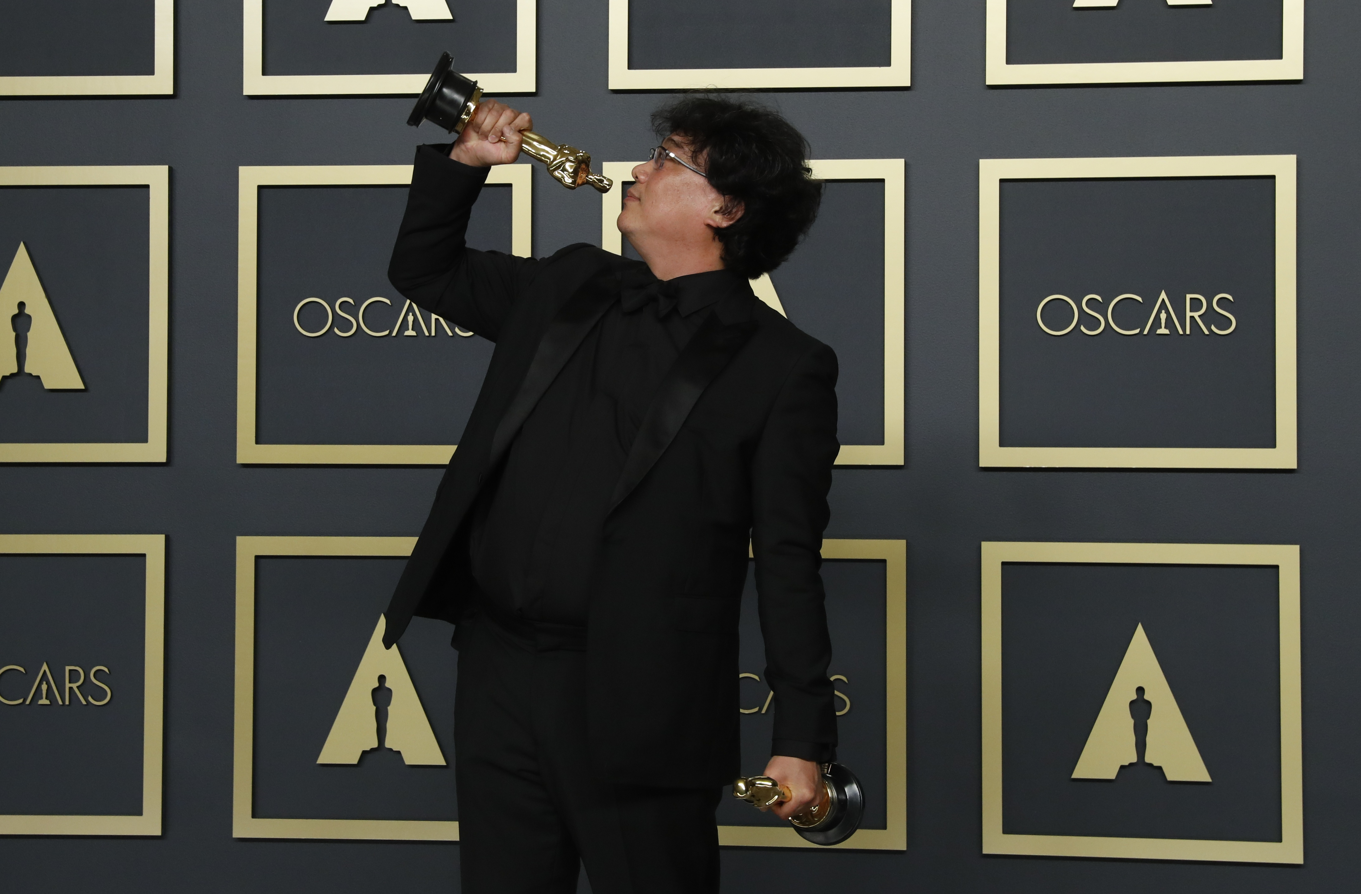 """Bong Joon Ho poses with two Oscars, one for Best Director and one for Best International Feature Film for """"Parasite"""" in the photo room during the 92nd Academy Awards in Hollywood, Los Angeles, California, U.S., February 9, 2020. REUTERS/Lucas Jackson"""