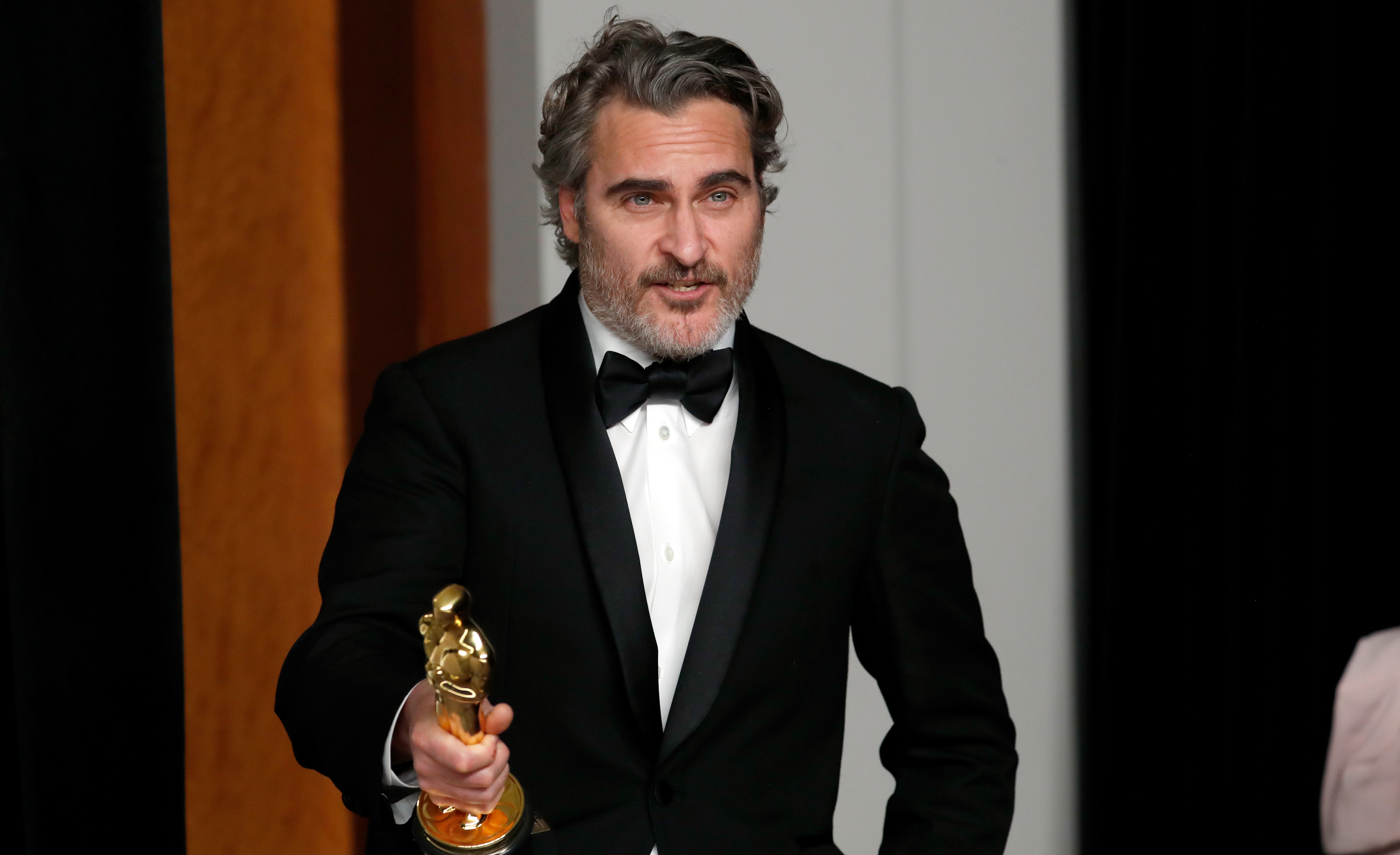 """Joaquin Phoenix poses with his Oscar for Best Actor in a Leading Role for """"Joker"""" in the photo room during the 92nd Academy Awards in Hollywood, Los Angeles, California, U.S., February 9, 2020. REUTERS/Lucas Jackson"""