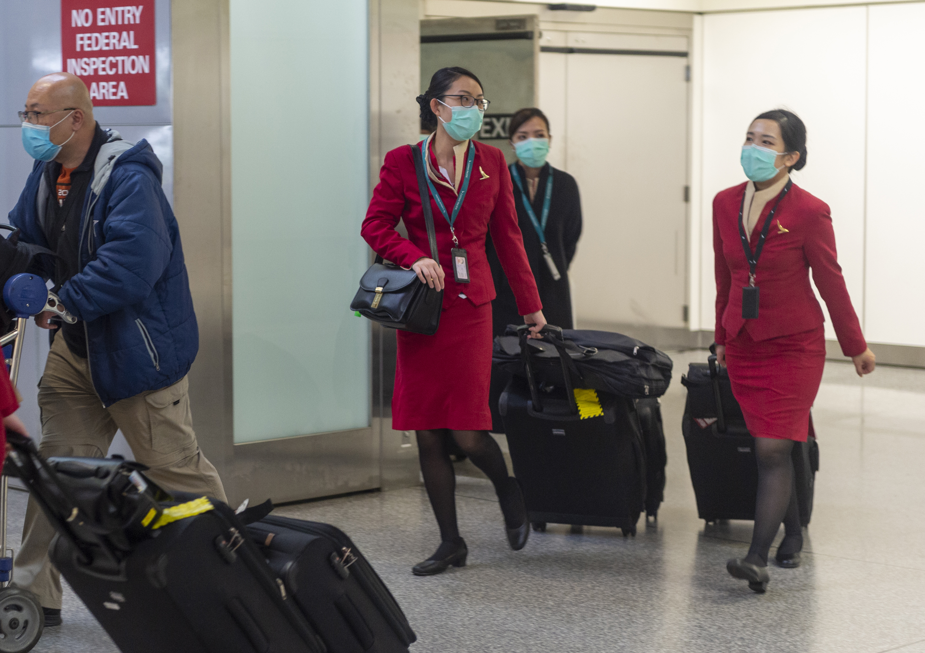 Cathay Pacific Airways cabin crew wearing face masks walk out of the international terminal at the San Francisco International Airport in Millbrae, California, United States on January 28, 2020. There are now 8,235 confirmed cases of coronavirus, with 171 death and 143 recovered. (Photo by Yichuan Cao/NurPhoto via Getty Images)