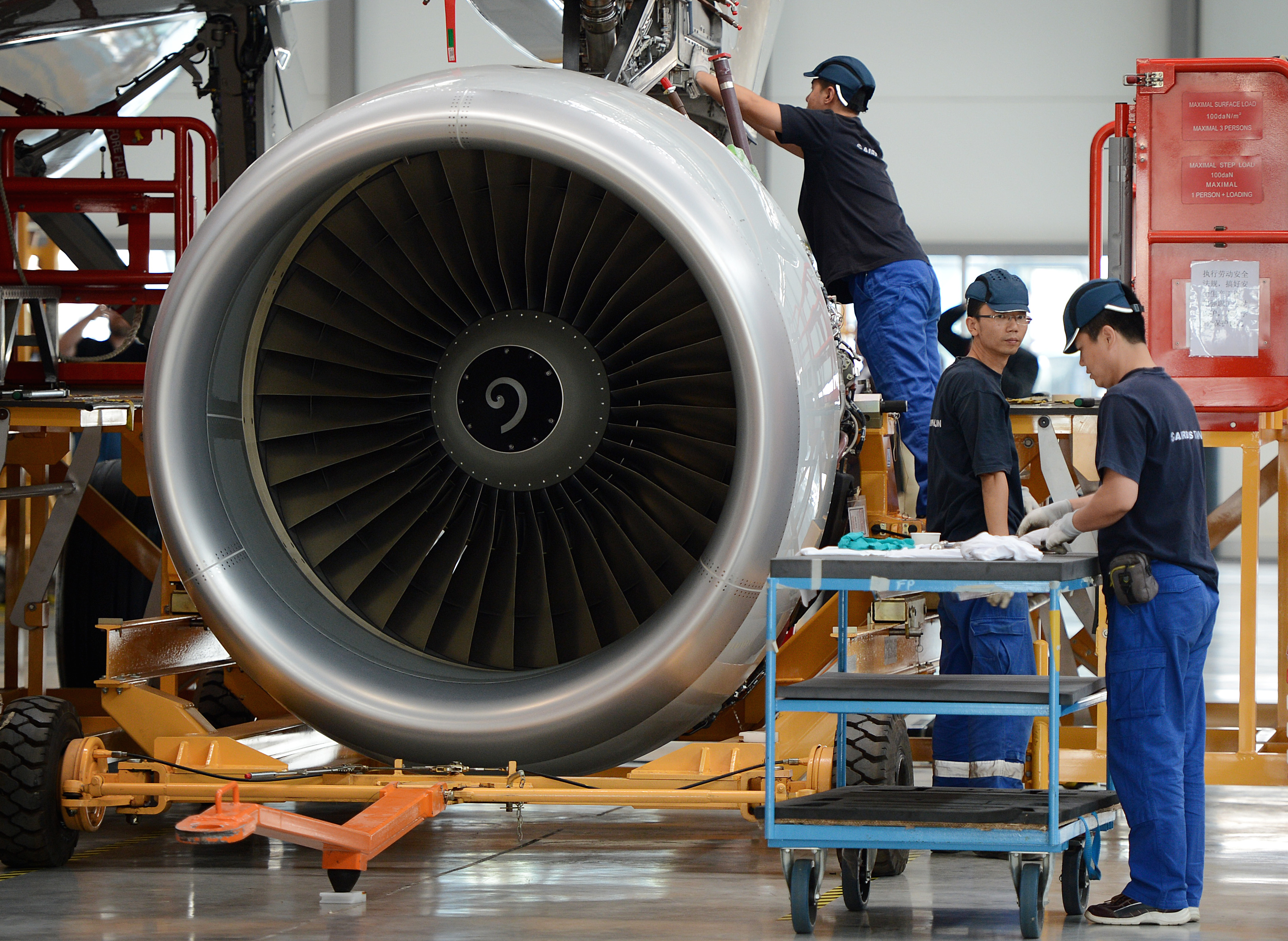 Airbus employees install an engine on an A320 plane under construction at the final assembly line of Airbus factory in the northern port city of Tianjin on June 13, 2012.  Tony Tyler who is the head of airline industry group IATA urged the European Union to postpone its controversial carbon tax scheme, amid warnings it could spark a trade war that would penalise Europe. China's aviation watchdog forbade Chinese airlines from participating in the so-called Emissions Trading Scheme (ETS).      AFP PHOTO/Mark RALSTON        (Photo credit should read MARK RALSTON/AFP/GettyImages)