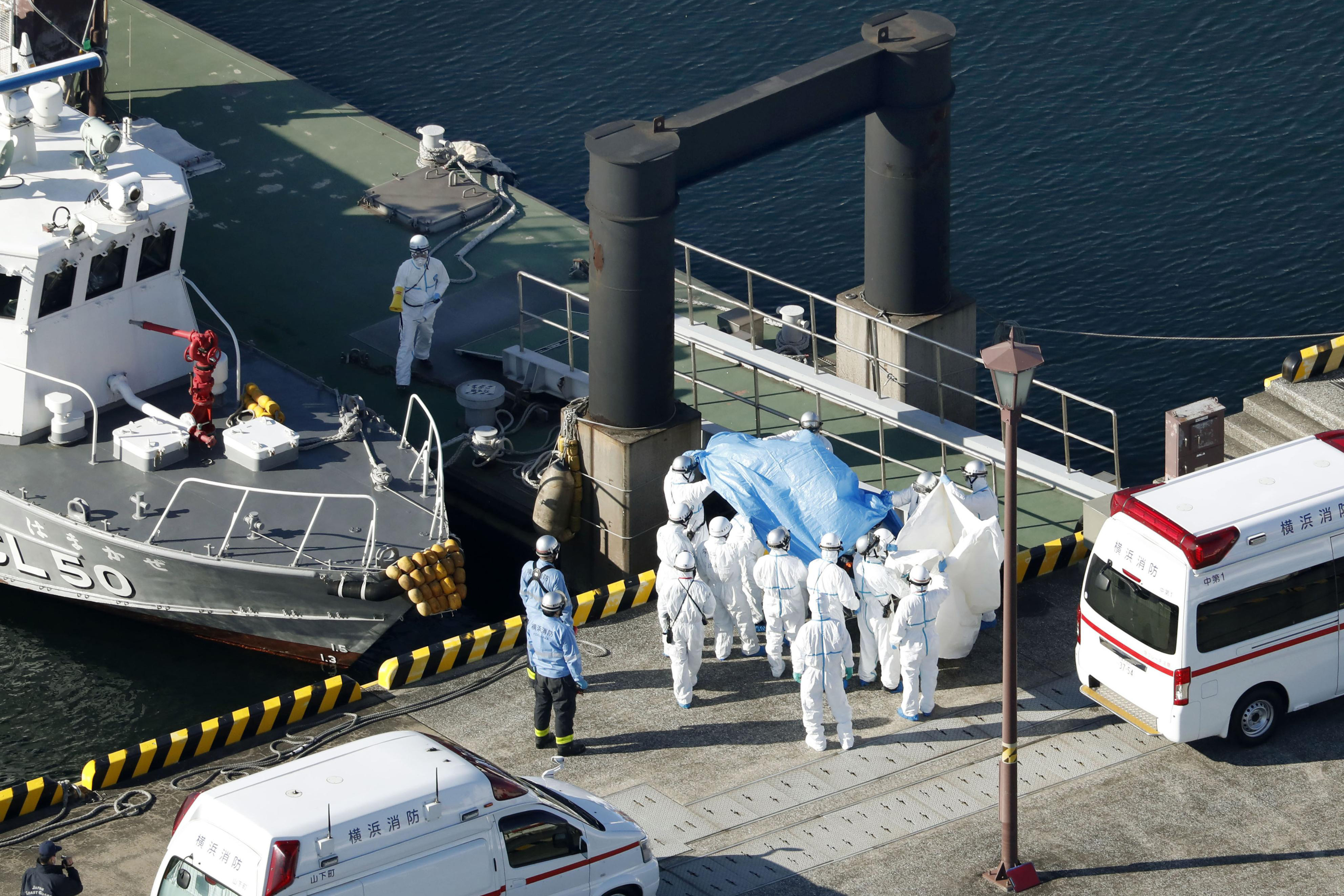 Medical workers in protective suits lead a passenger tested positive for a new coronavirus from the cruise ship Diamond Princess at Yokohama Port in Yokohama, south of Tokyo, Wednesday, Feb. 5, 2020. Japan said Wednesday 10 people on the cruise ship have tested positive for the new virus and were being taken to hospitals. Health Minister Nobukatsu Kato said all the 3,700 people and passengers on the ship will be quarantined on board for up to 14 days under Japanese law. (Hiroko Harima/Kyodo News via AP)