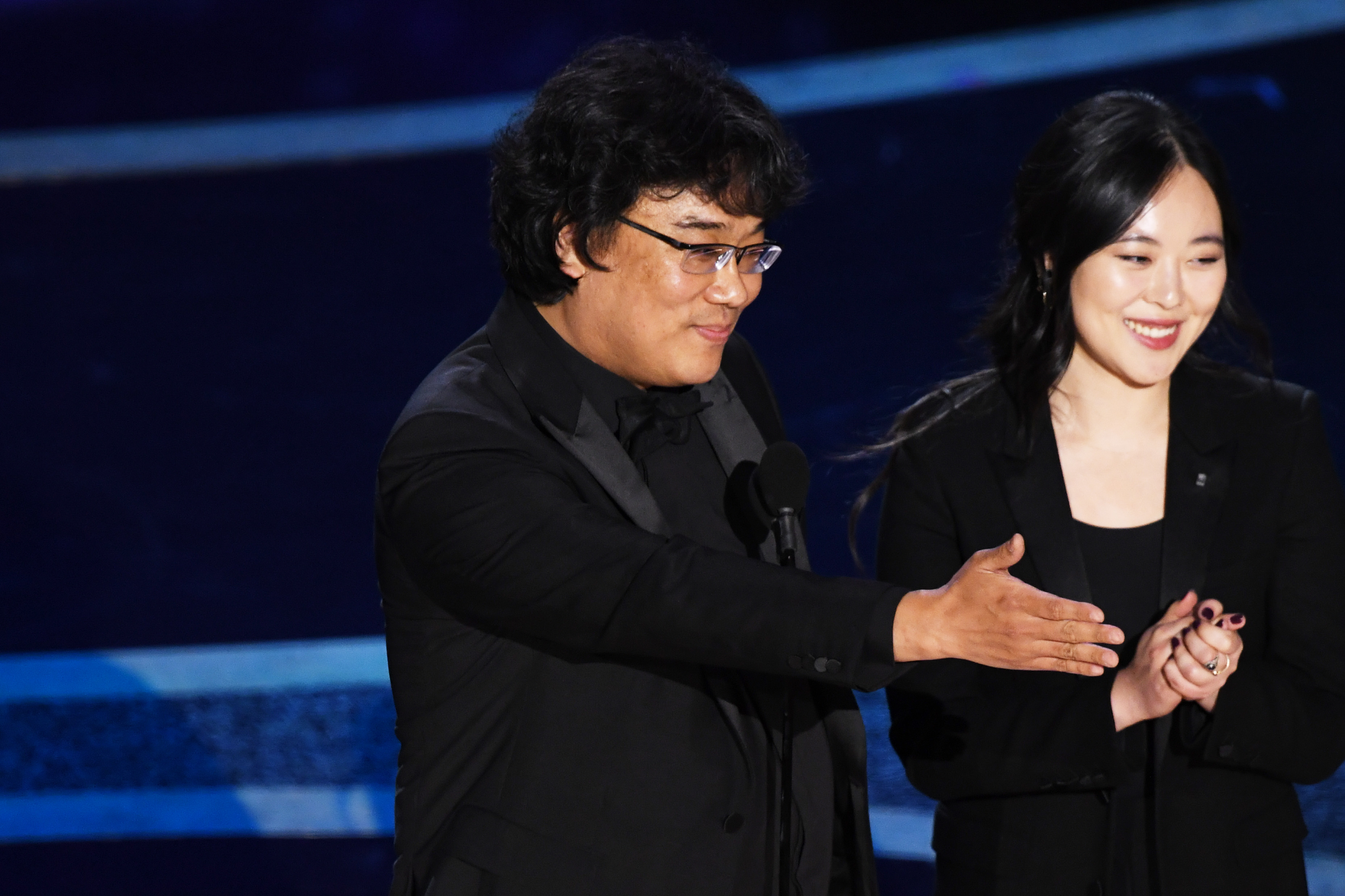 HOLLYWOOD, CALIFORNIA - FEBRUARY 09: Bong Joon-ho accepts the Directing award for 'Parasite' with interpreter Sharon Choi onstage during the 92nd Annual Academy Awards at Dolby Theatre on February 09, 2020 in Hollywood, California. (Photo by Kevin Winter/Getty Images)