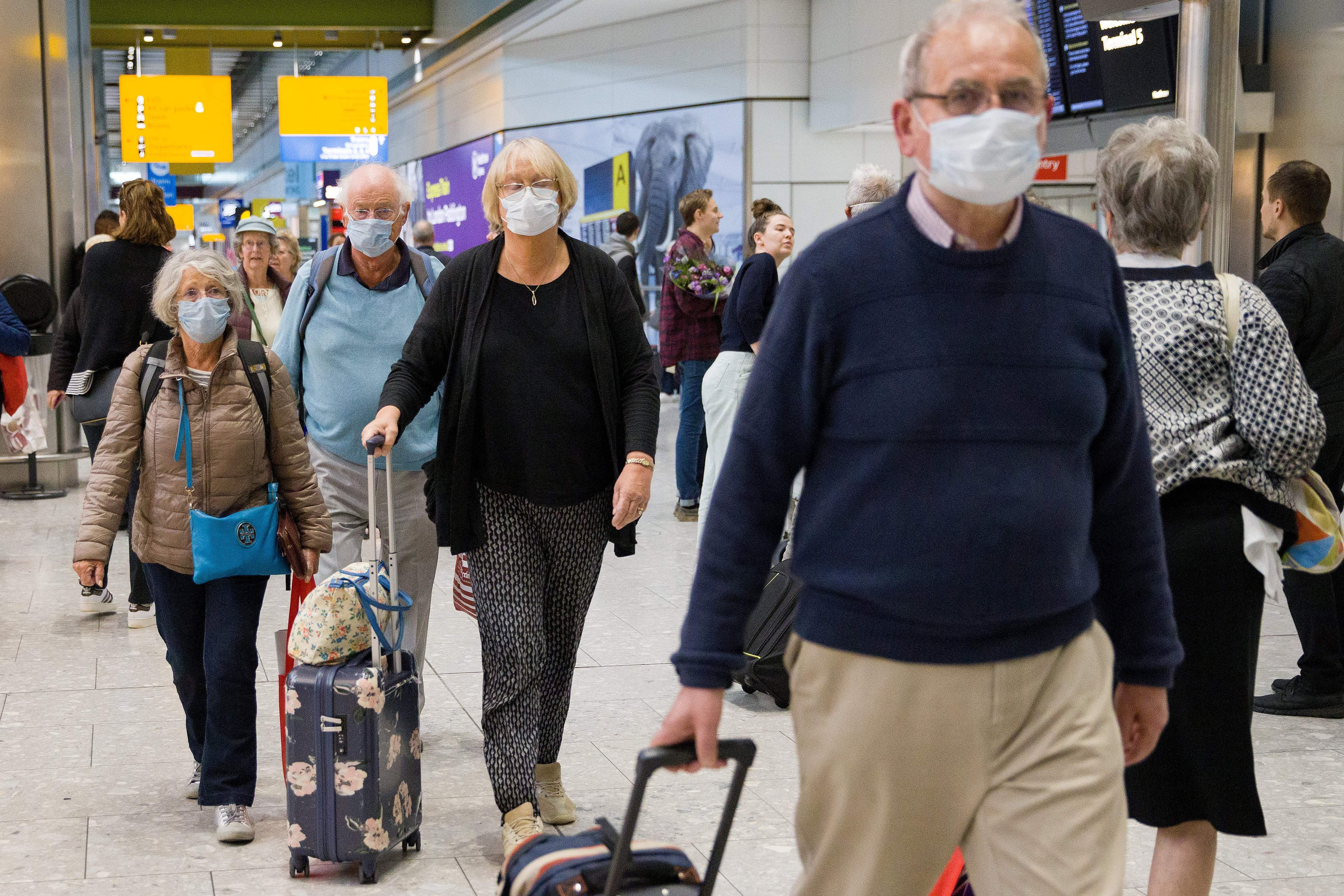 Travellers who had been aboard the Braemar cruise ship, operated by Fred Olsen Cruise Lines, and wearing face masks as a precautionary measure against covid-19, react as they arrive at Heathrow Airport in London on March 19, 2020, after being flown back from Cuba. - The MS Braemar had more than 1,000 people aboard including five confirmed coronavirus cases and more than 50 people in isolation due to showing flu-like symptoms. (Photo by Tolga AKMEN / AFP) (Photo by TOLGA AKMEN/AFP via Getty Images)