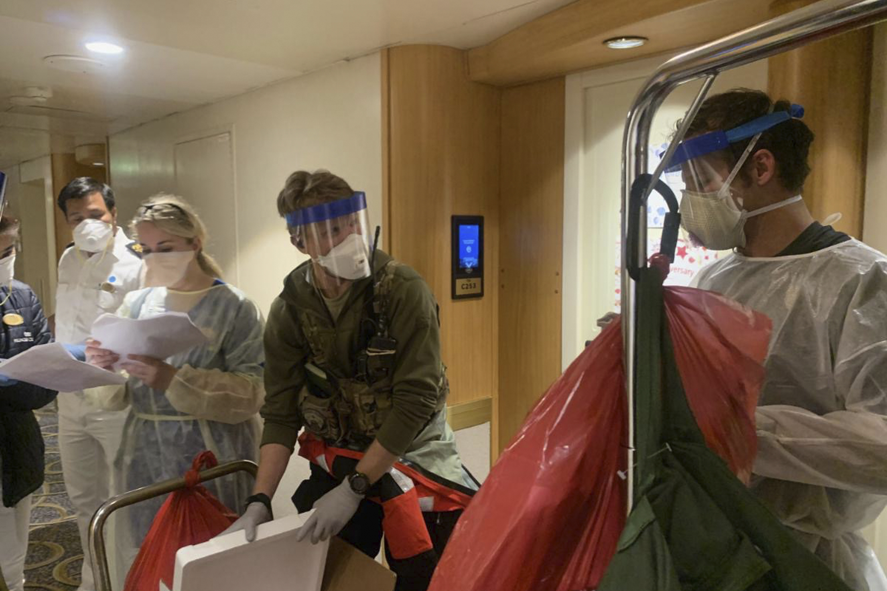 In this Thursday, March 5, 2020, photo, released by the California National Guard, Guardian Angels, a group of medical personnel with the 129th Rescue Wing, working alongside individuals from the Centers for Disease Control and Prevention, don protective equipment after delivering virus testing kits to the Grand Princess cruise ship off the coast of California. Passengers on a cruise ship off the California coast were instructed to stay in their cabins as they awaited test results Friday that could show whether the coronavirus is circulating among the more than 3,500 people aboard. (Chief Master Sgt. Seth Zweben/California National Guard via AP)