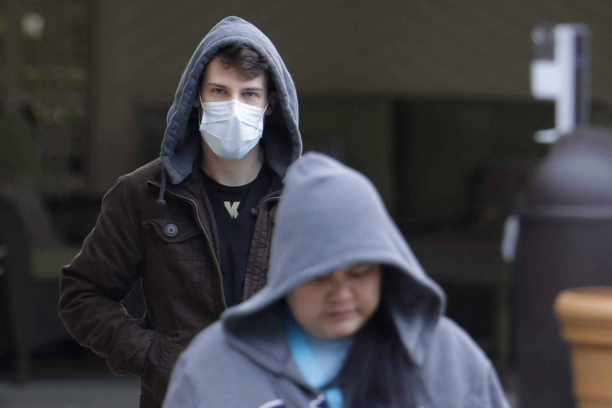 A man wearing a mask walks away from the entrance of the Life Care Center in Kirkland, Wash., near Seattle, Tuesday, March 3, 2020. The facility has been tied to several confirmed cases of the COVID-19 coronavirus. (AP Photo/Ted S. Warren)