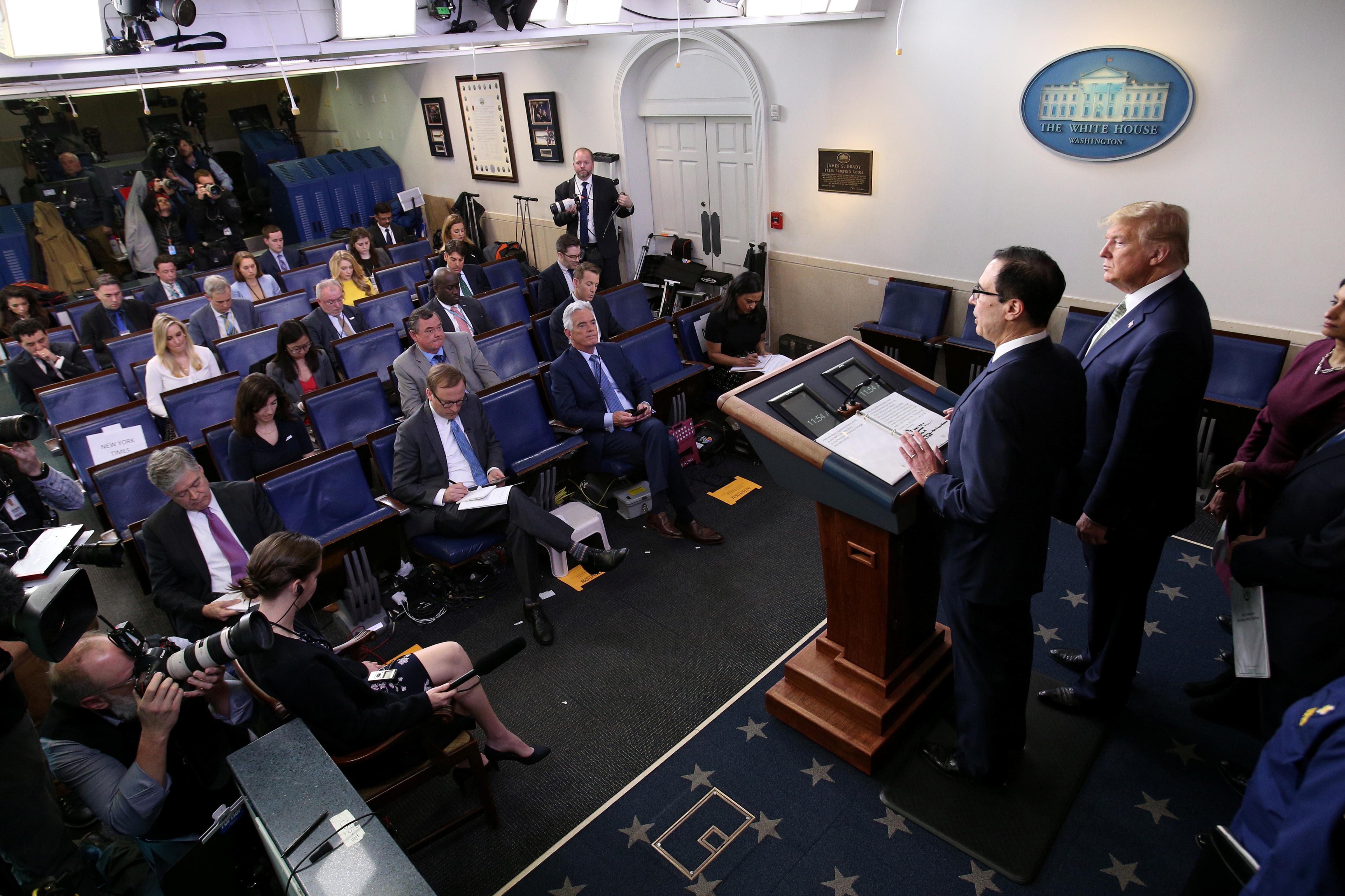 U.S. President Donald Trump looks on as Treasury Secretary Steven Mnuchin addresses the daily coronavirus (COVID-19) briefing at the White House in Washington, U.S., March 17, 2020. REUTERS/Jonathan Ernst