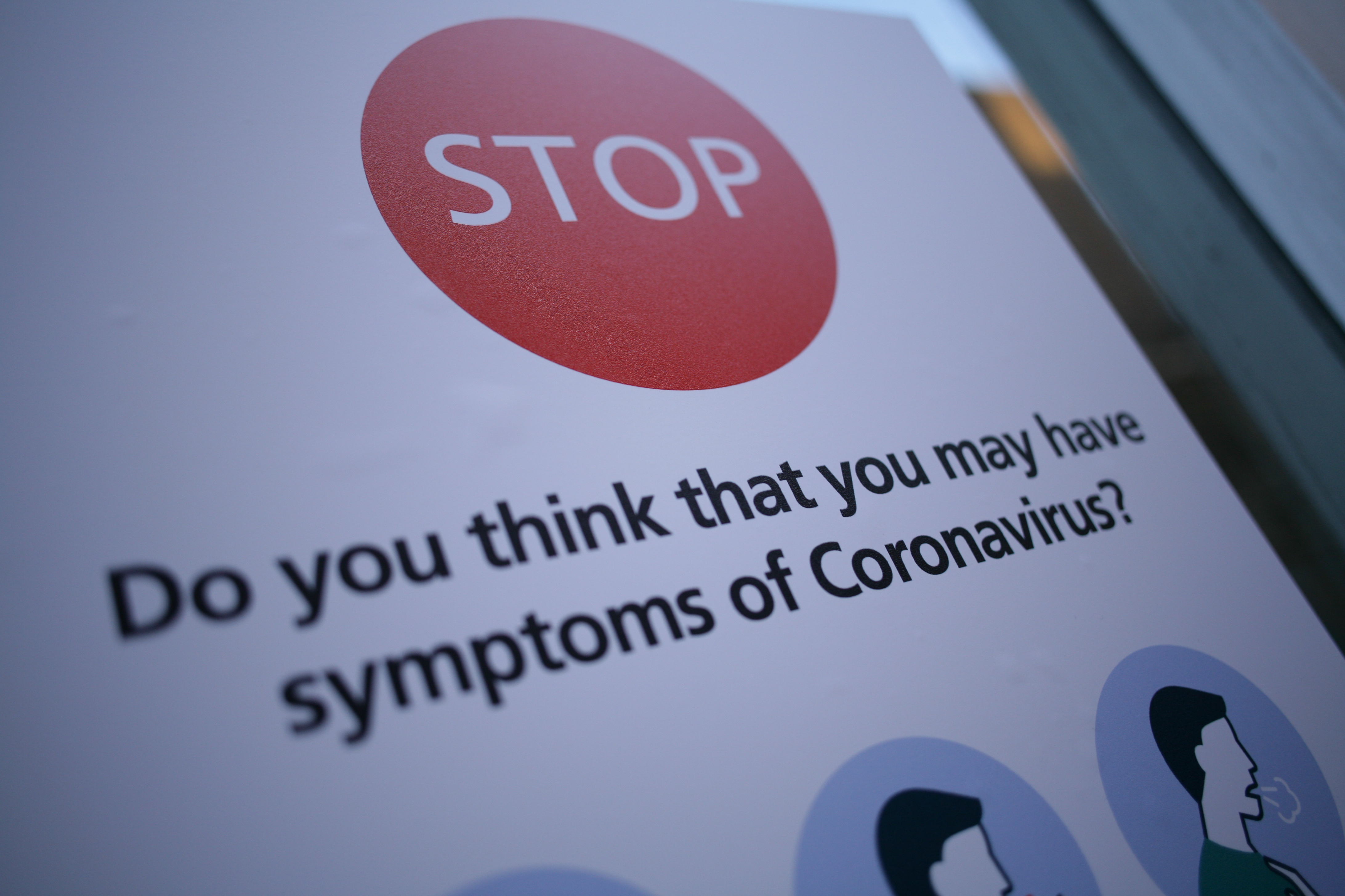 A notice instructs people with symptoms of the covid-19 coronavirus not to enter St Mary's Hospital in London, England, on March 11, 2020. The hospital houses a dedicated 'coronavirus pod' isolation unit for symptomatic patients. In the UK, 460 people have now been confirmed to have the virus. Six patients with coronavirus have so far died in hospitals around the country. The World Health Organisation (WHO) meanwhile today officially designated the global spread of the illness as a pandemic. (Photo by David Cliff/NurPhoto via Getty Images)