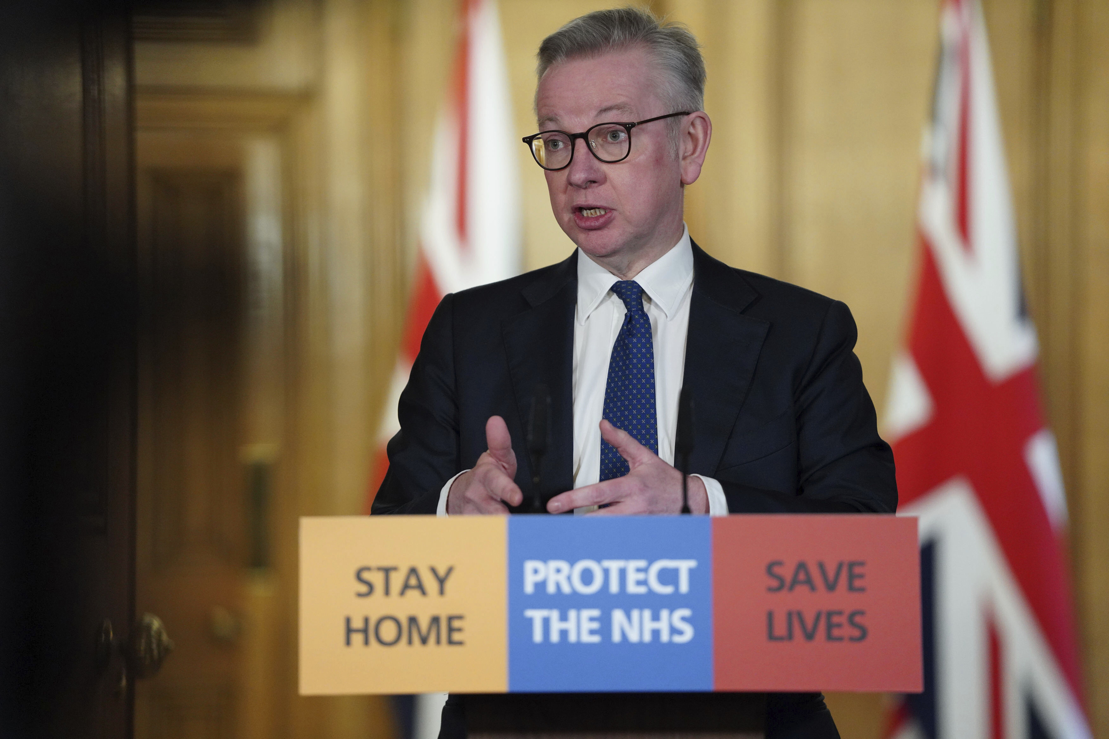 In this image made available by British government because no media allowed into 10 Downing Street because of the coronavirus pandemic, showing British lawmaker Michael Gove holding a Digital Press Conference on COVID-19, in 10 Downing Street, London, Friday March 27, 2020. Prime Minister Boris Johnson has tested positive for the COVID-19 coronavirus Friday along with other members of the government, and has self isolated. (Pippa Fowles / No 10 Downing Street via AP)