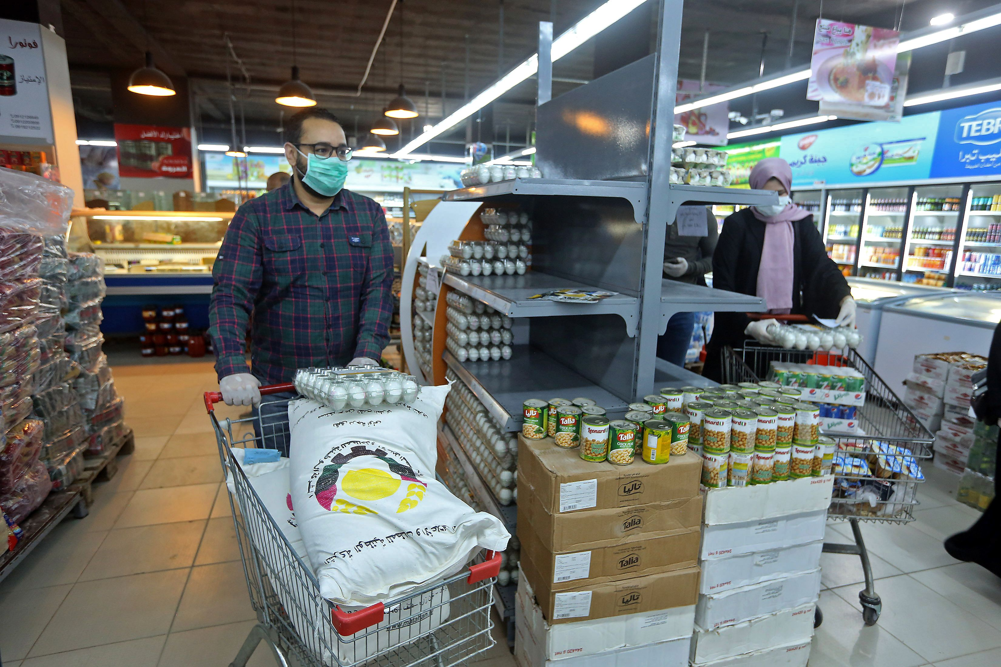 Customers wearing face masks and gloves amid concerns over the spread of the COVID-19 coronavirus, shop at a supermarket in the Libyan capital on March 25, 2020. - Libya has reported its first case of the novel coronavirus, a particular source of concern in the North African country where civil war has badly degraded the public healthcare system. (Photo by Mahmud TURKIA / AFP) (Photo by MAHMUD TURKIA/AFP via Getty Images)
