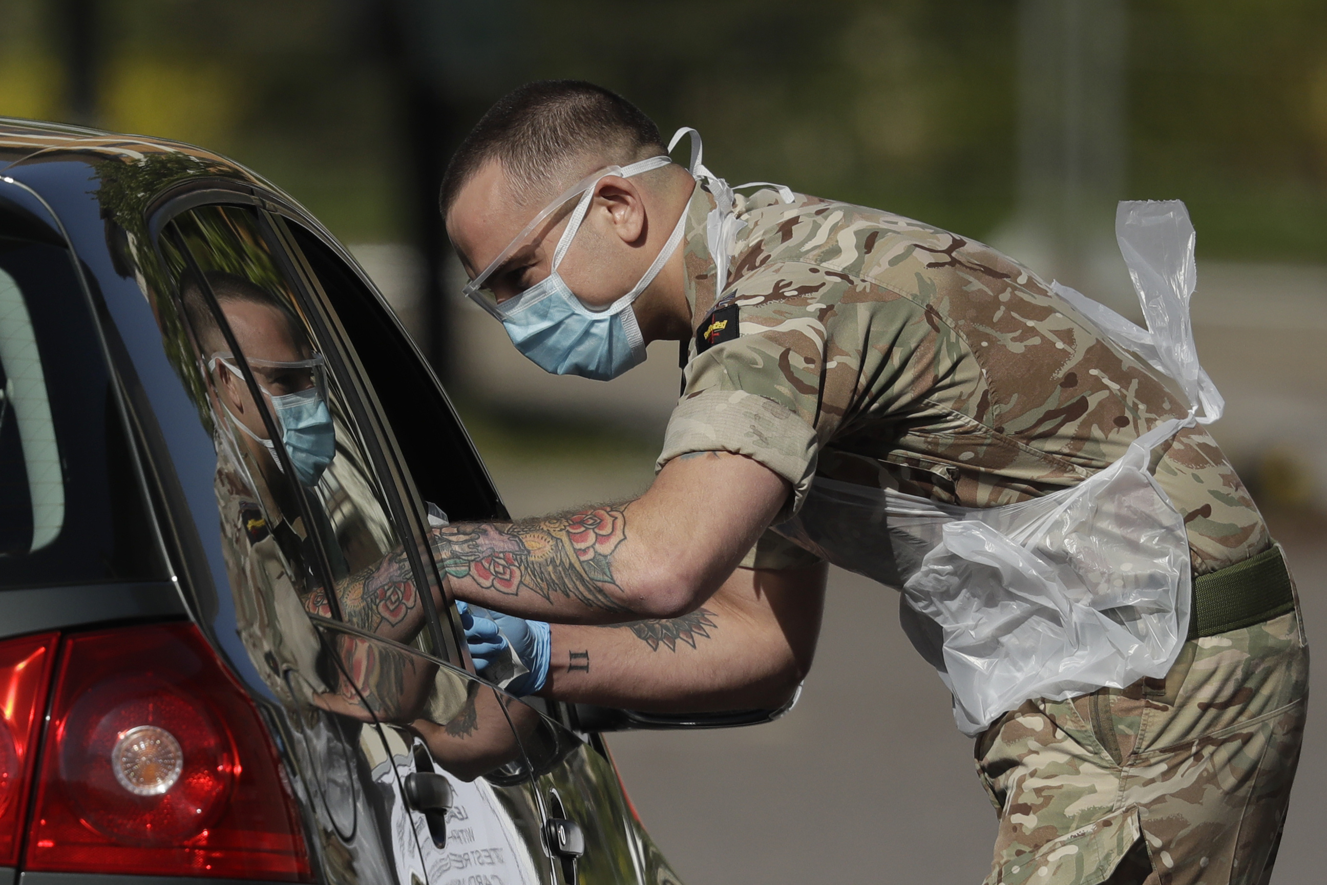A NHS (National Health Service) worker or care worker is tested by a soldier for COVID-19 at a drive-through testing centre in a car park at Chessington World of Adventures, in Chessington, Greater London, Monday, April 20, 2020. The highly contagious COVID-19 coronavirus has impacted on nations around the globe, many imposing self isolation and exercising social distancing when people move from their homes. (AP Photo/Matt Dunham)