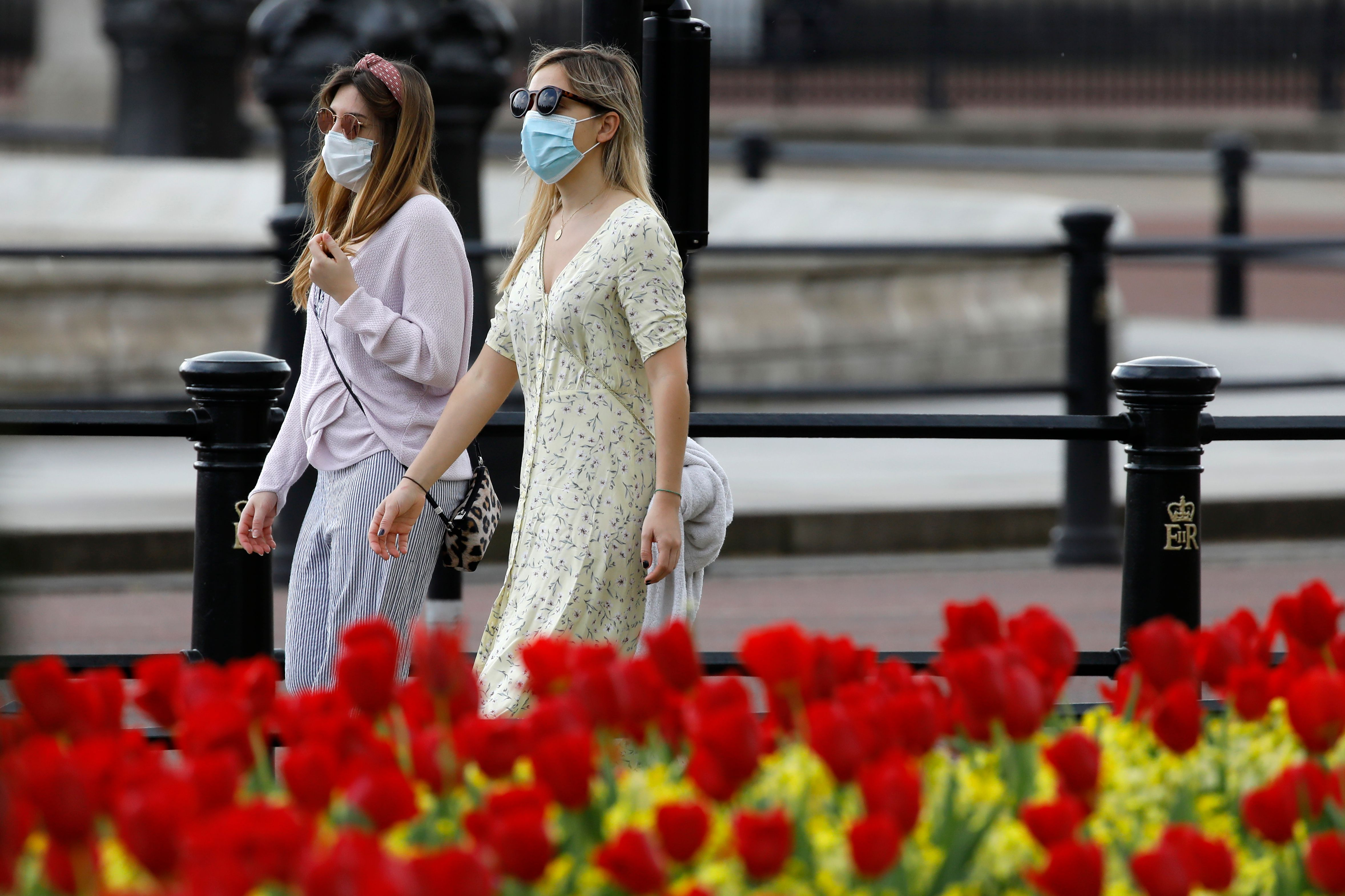 Two women wear protective face masks as they walk past the flowers outside Buckingham Palace in London on April 12, 2020, during the nationwide lockdown to combat the novel coronavirus pandemic. - The Prime Minister left hospital on Sunday to convalesce from coronavirus at Chequers, the country estate of British prime ministers, officials said, a week after he was admitted and then spent three days in intensive care. (Photo by Tolga AKMEN / AFP) (Photo by TOLGA AKMEN/AFP via Getty Images)