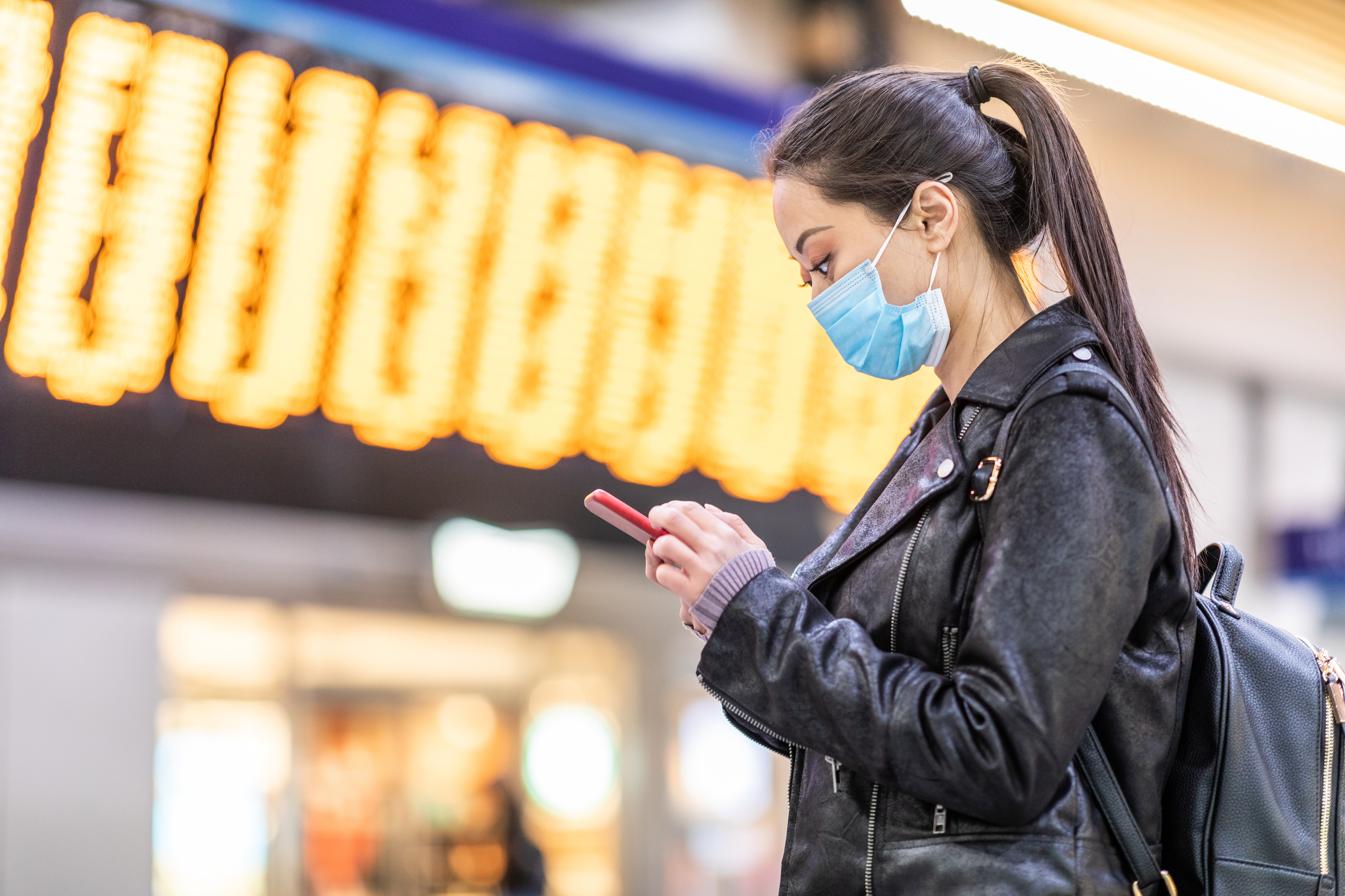 Chinese woman wearing face mask at train station to protect from smog and virus - young asian woman looking at her smartphone with departure arrivals board behind - health and travel concepts