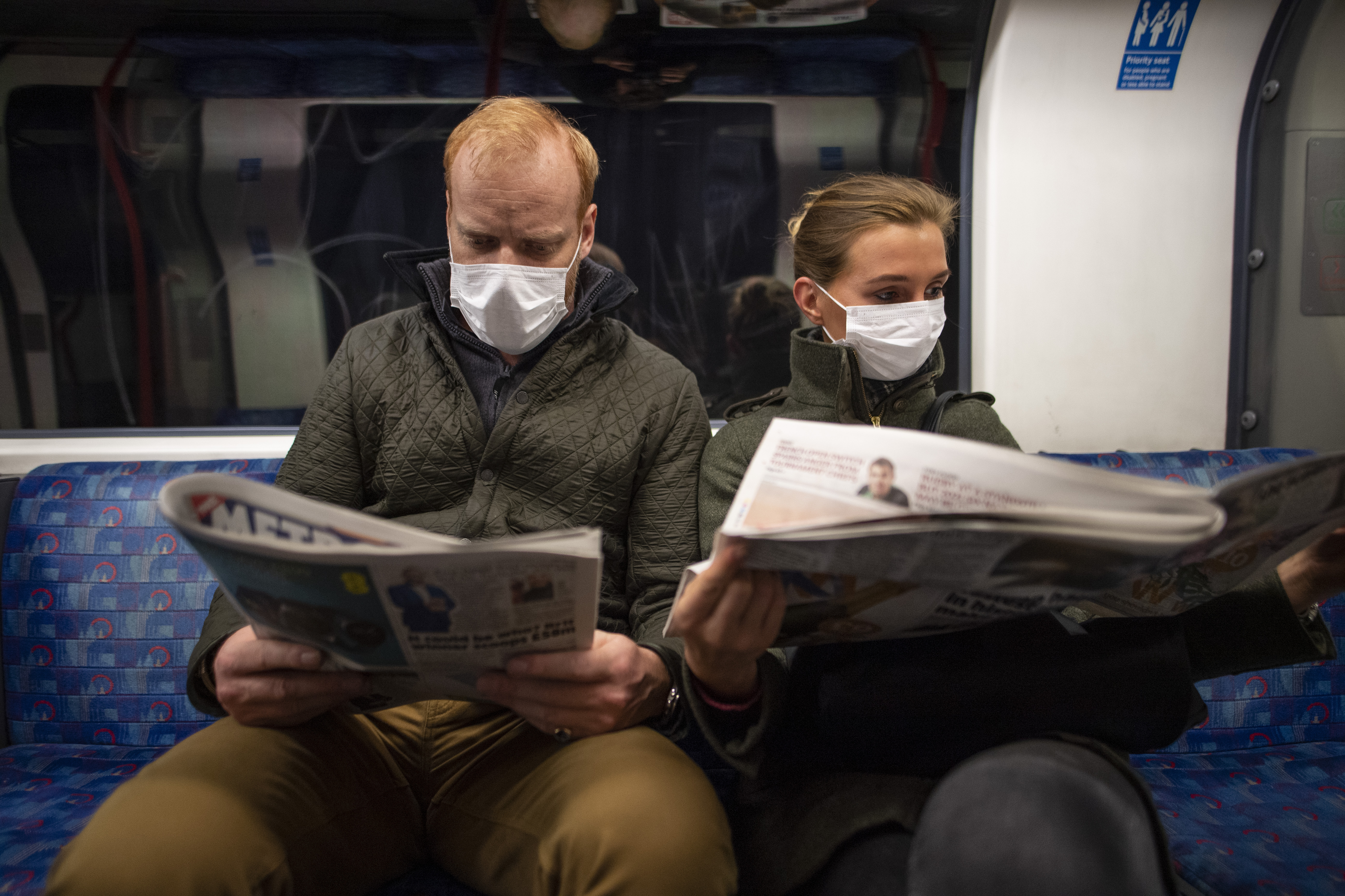 LONDON, ENGLAND - MARCH 19: A couple sit on the Central Line Tube wearing protective face masks while reading a newspaper on March 19, 2020 in London, England. Transport for London announced the closure of up to 40 stations as officials advised against non-essential travel. Bus and London Overground service will also be reduced. (Photo by Justin Setterfield/Getty Images)