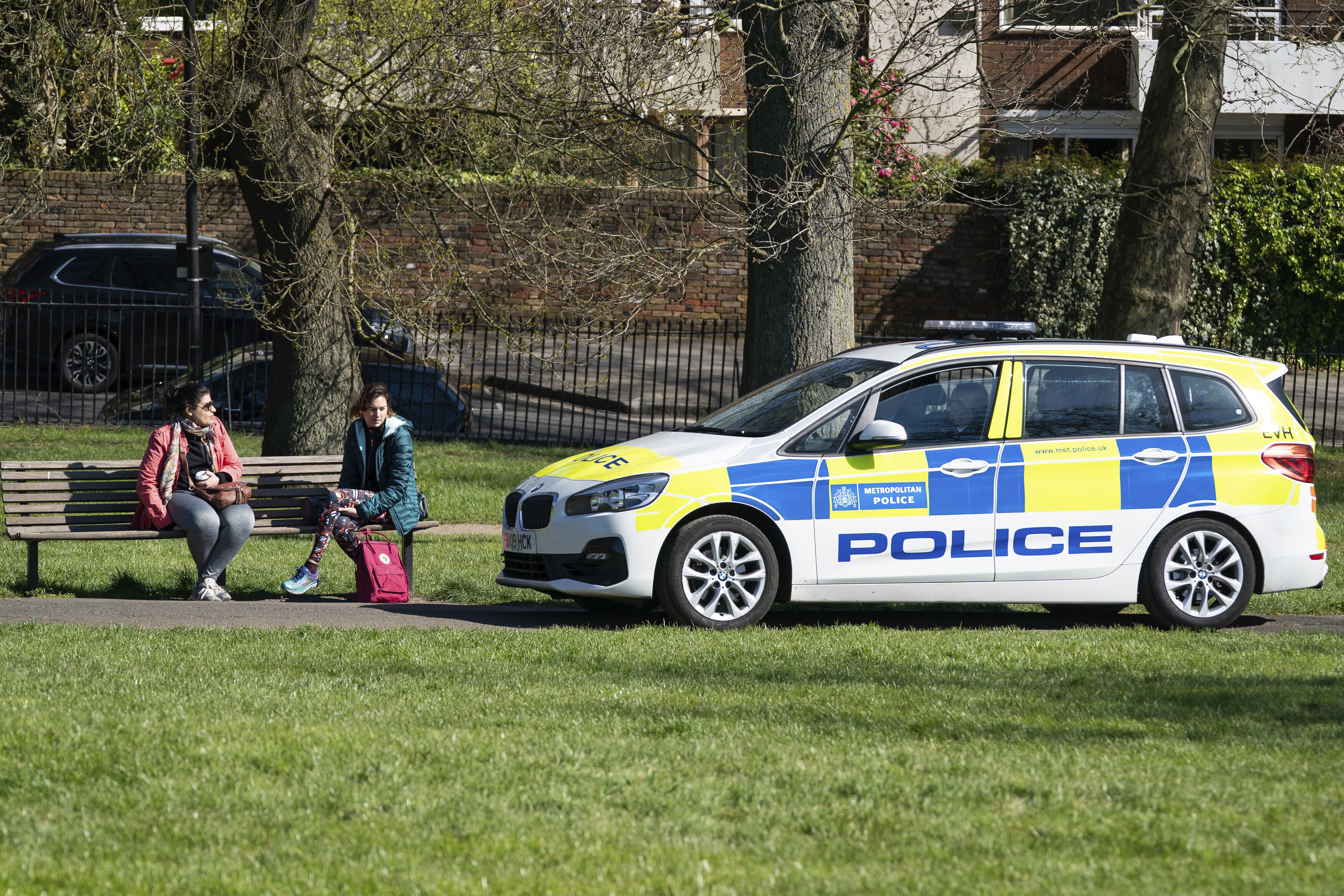 Police ask two women to move on in Primrose Hill, London, Sunday April 5, 2020, as the UK continues in lockdown to help curb the spread of the coronavirus. The new coronavirus causes mild or moderate symptoms for most people, but for some, especially older adults and people with existing health problems, it can cause more severe illness or death.(Aaron Chown/PA via AP)