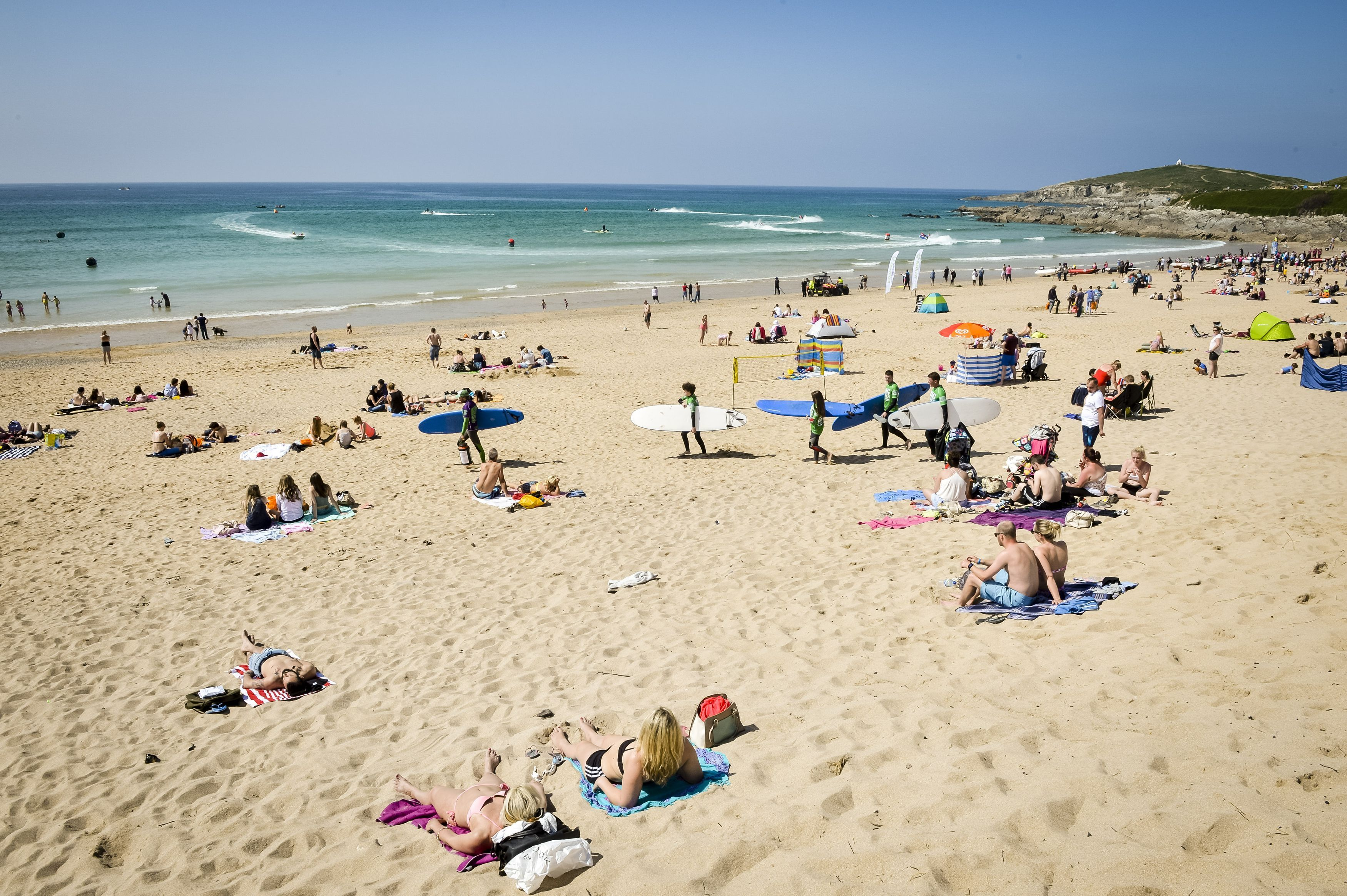 People relax in the sun at Fistral Beach, Cornwall.