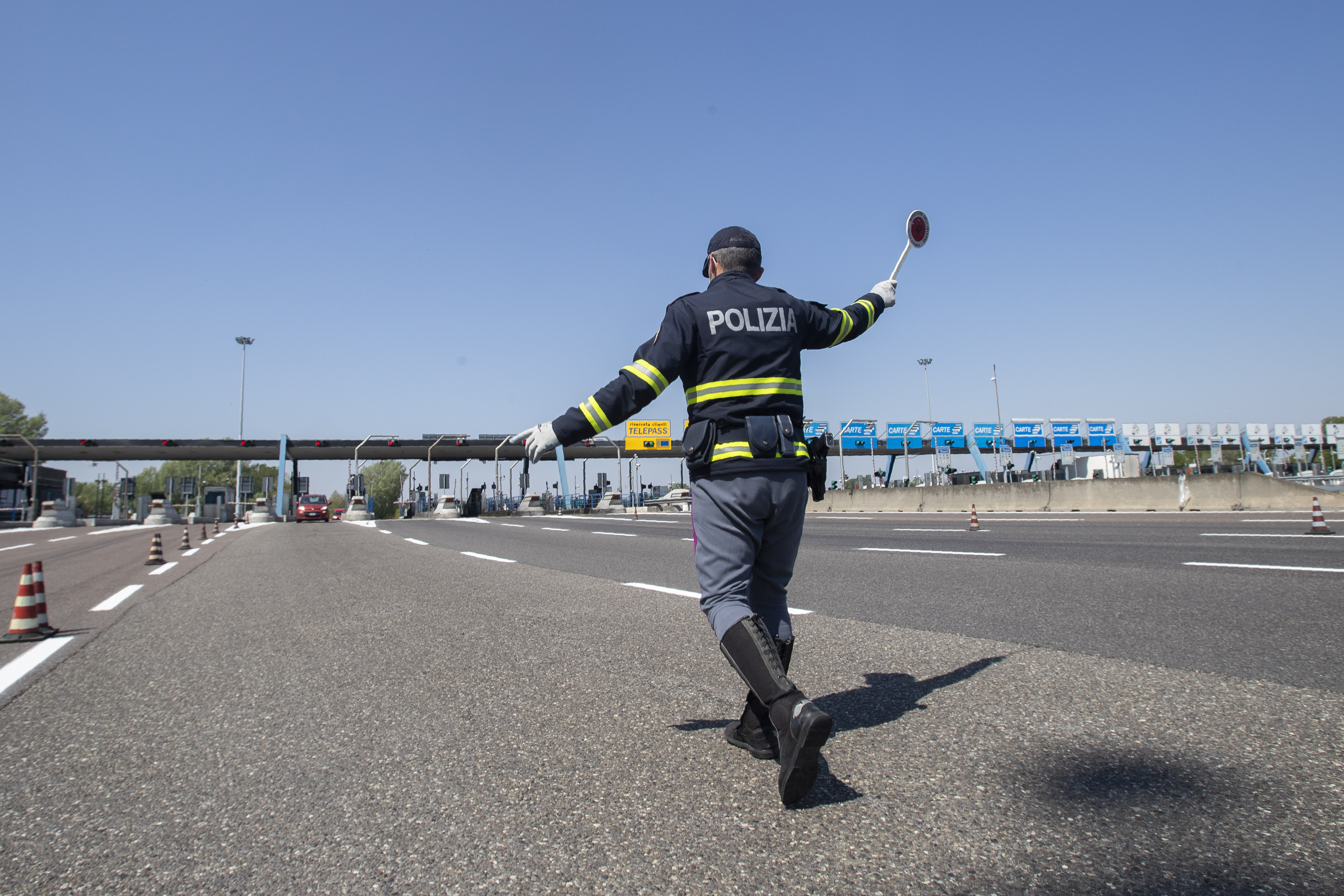 Police officers stop cars at the Melegnano highway barrier entrance, near Milan, Italy, Saturday, April 11, 2020. Using helicopters, drones and stepped-up police checks to make sure Italians don't slip out of their homes for the Easter holiday weekend, Italian authorities are doubling down on their crackdown against violators of the nationwide lockdown decree. The new coronavirus causes mild or moderate symptoms for most people, but for some, especially older adults and people with existing health problems, it can cause more severe illness or death. (AP Photo/Luca Bruno)