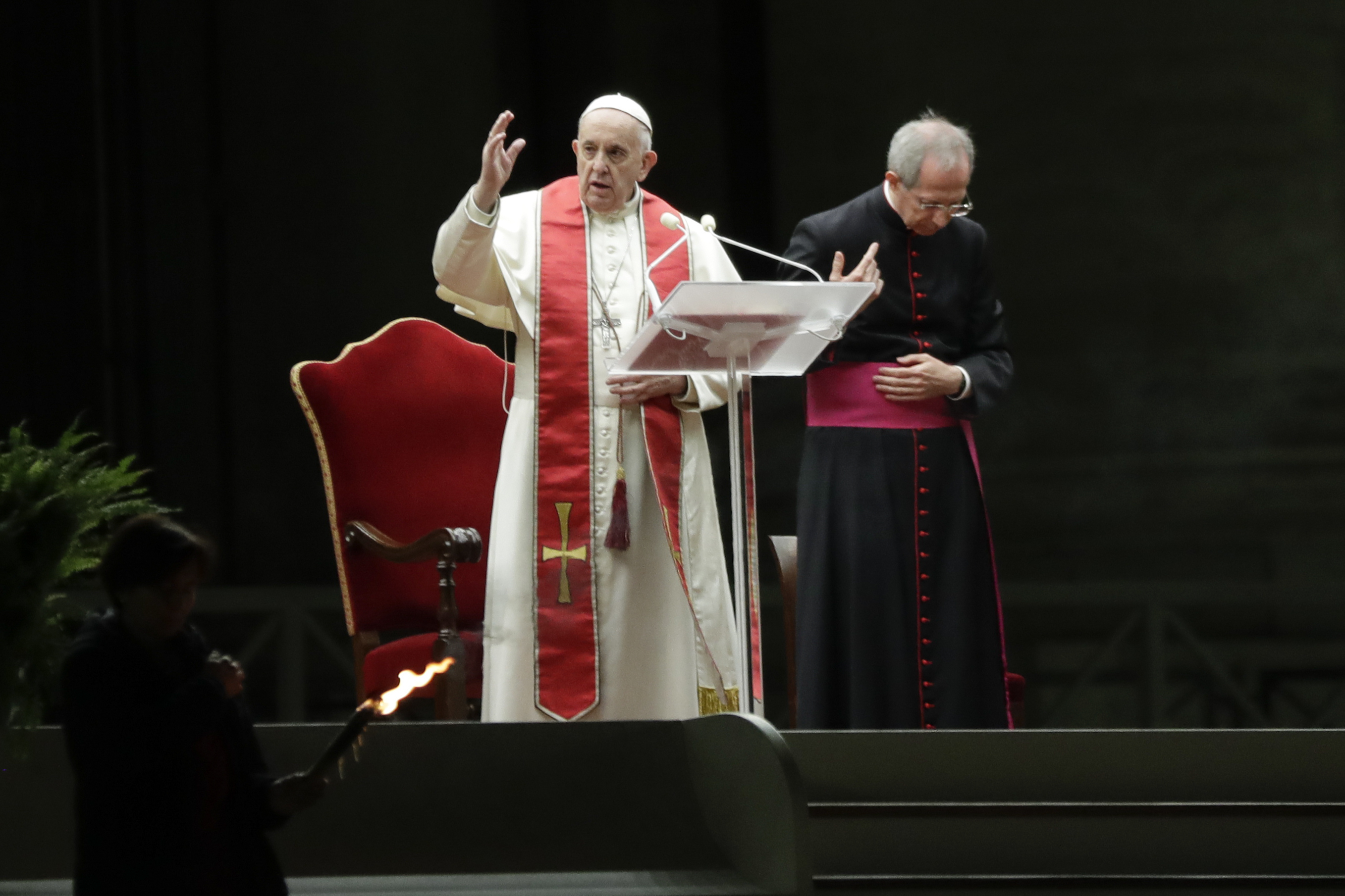 Pope Francis is flanked by Mons. Guido Marini as he delivers his blessing during the Via Crucis - or Way of the Cross - ceremony in front of St. Peter's Basilica, empty of the faithful following Italy's ban on gatherings during a national lockdown to contain contagion, at the Vatican, Friday, April 10, 2020. (AP Photo/Andrew Medichini, Pool)