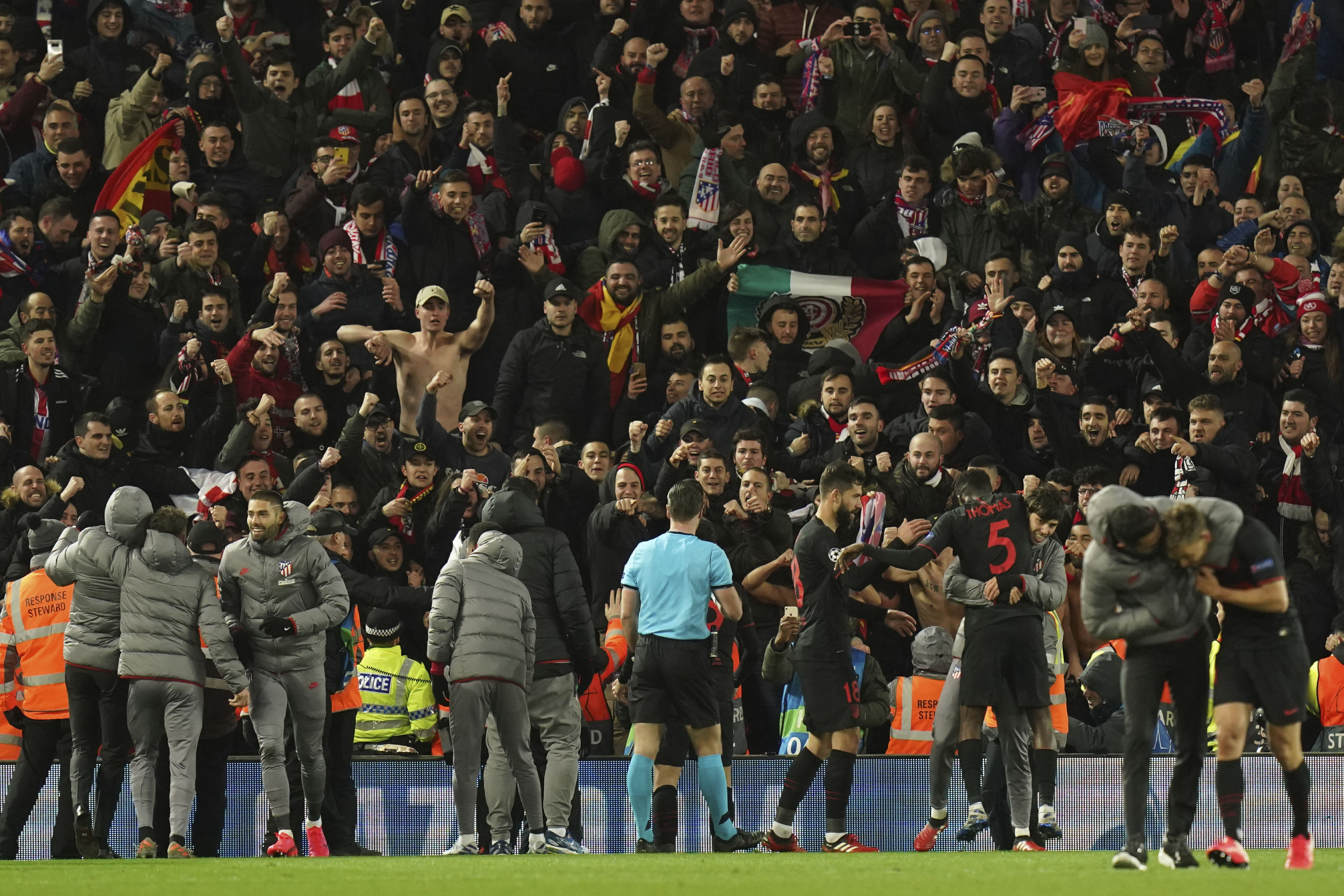 Atletico Madrid players celebrate at the end of the second leg, round of 16, Champions League soccer match between Liverpool and Atletico Madrid at Anfield stadium in Liverpool, England, Wednesday, March 11, 2020. (AP Photo/Jon Super)